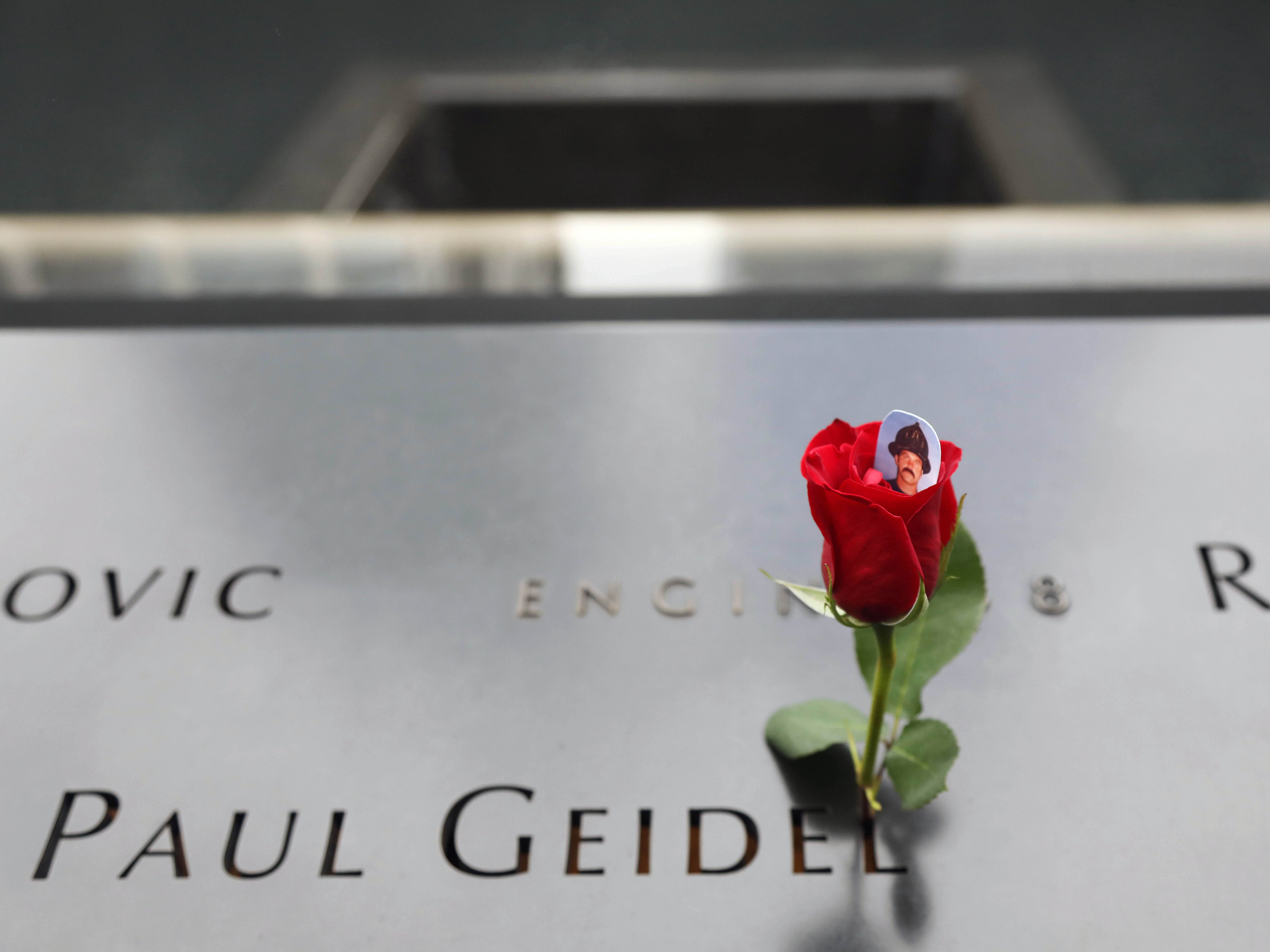 A flower is placed on the South Tower Memorial by the name of Paul Geidel with Engine Co. 8 during ceremonies at the National September 11 Memorial on Sept. 11, 2018, in New York.
