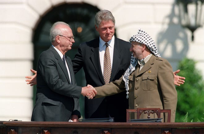 President Bill Clinton stands between Palestinian leader Yasser Arafat and Israeli Prime Minister Yitzhak Rabin on Sept. 13, 1993.