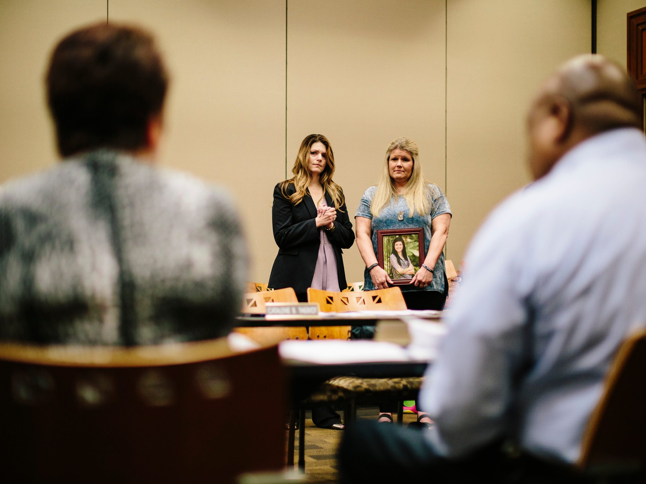 Jamie Reavis, right, of Jefferson Parish, Louisiana, holds a photograph of her daughter as she speaks during a meeting of the Louisiana Crime Victims Reparations Board on May 1, 2017 in Baton Rouge, Louisiana. Reavis' daughter Taylor Friloux was murdered during a robbery at a fast-food restaurant where she worked. At left is Nancy Michel, head of the Jefferson Parish District Attorney's Office Victim/Witness Assistance Division.
