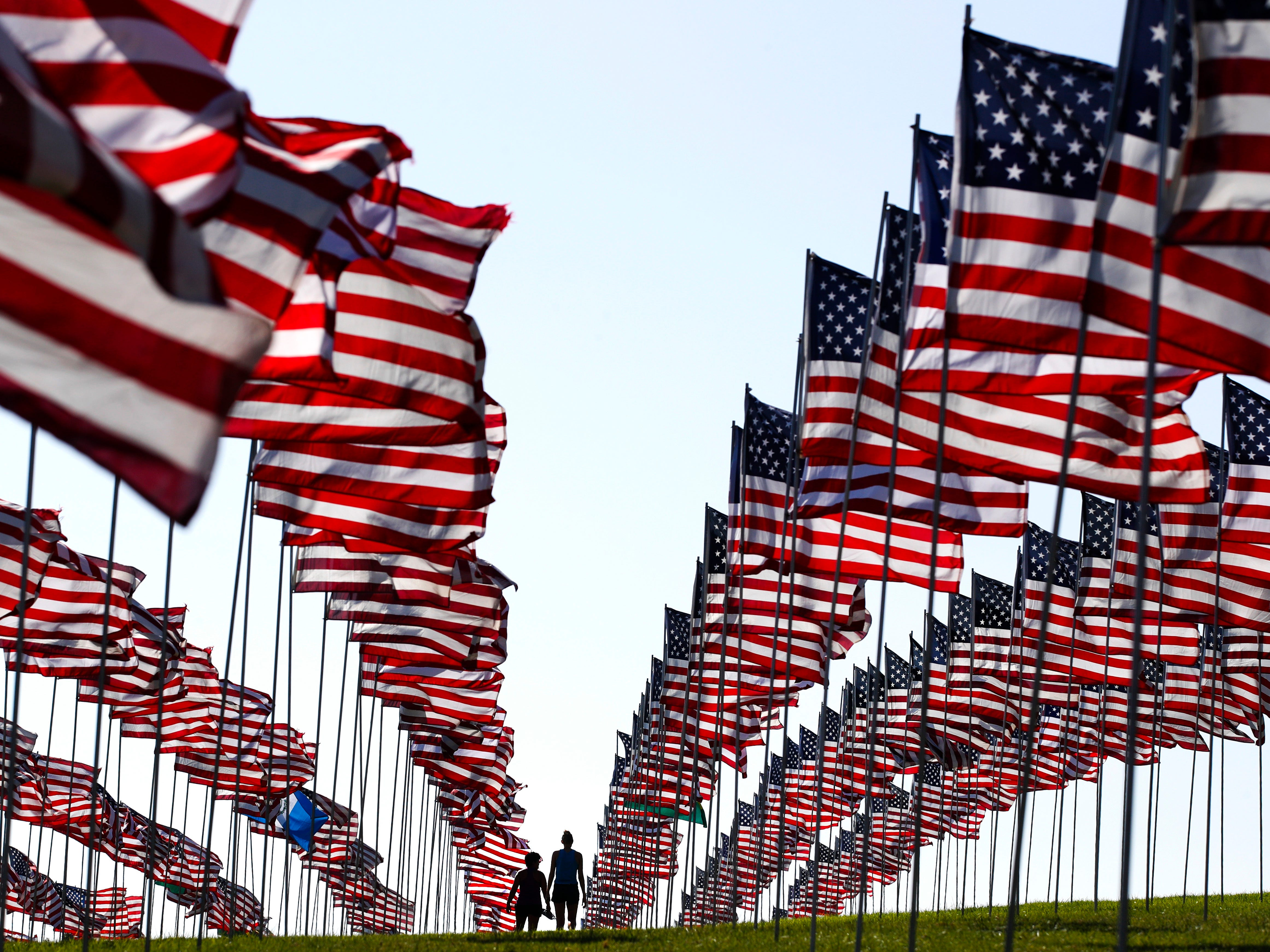 Bianca Burton, center left, and Erin Schultheis walk around the Pepperdine University's annual display of flags honoring the victims of the 9/11 terrorist attacks, Monday, Sept. 10, 2018, in Malibu, Calif. Terrorists used hijacked planes to crash Sept. 11, 2001, into the World Trade Centers, the Pentagon and a field in Pennsylvania. Nearly 3,000 people were killed in the attacks. (AP Photo/Jae C. Hong) ORG XMIT: CAJH101