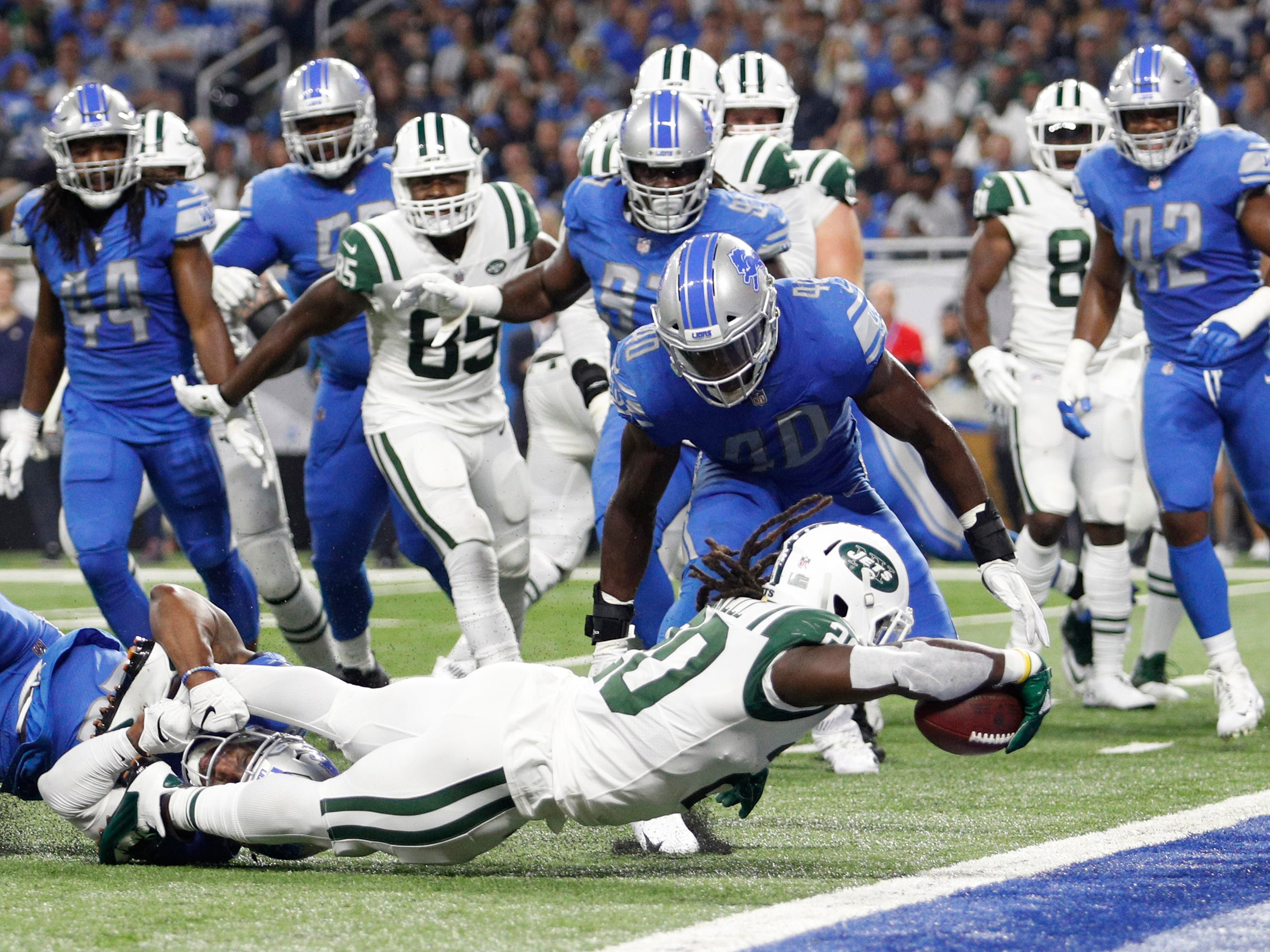 New York Jets running back Isaiah Crowell reaches over the goal line for a touchdown during the first quarter against the Detroit Lions at Ford Field.