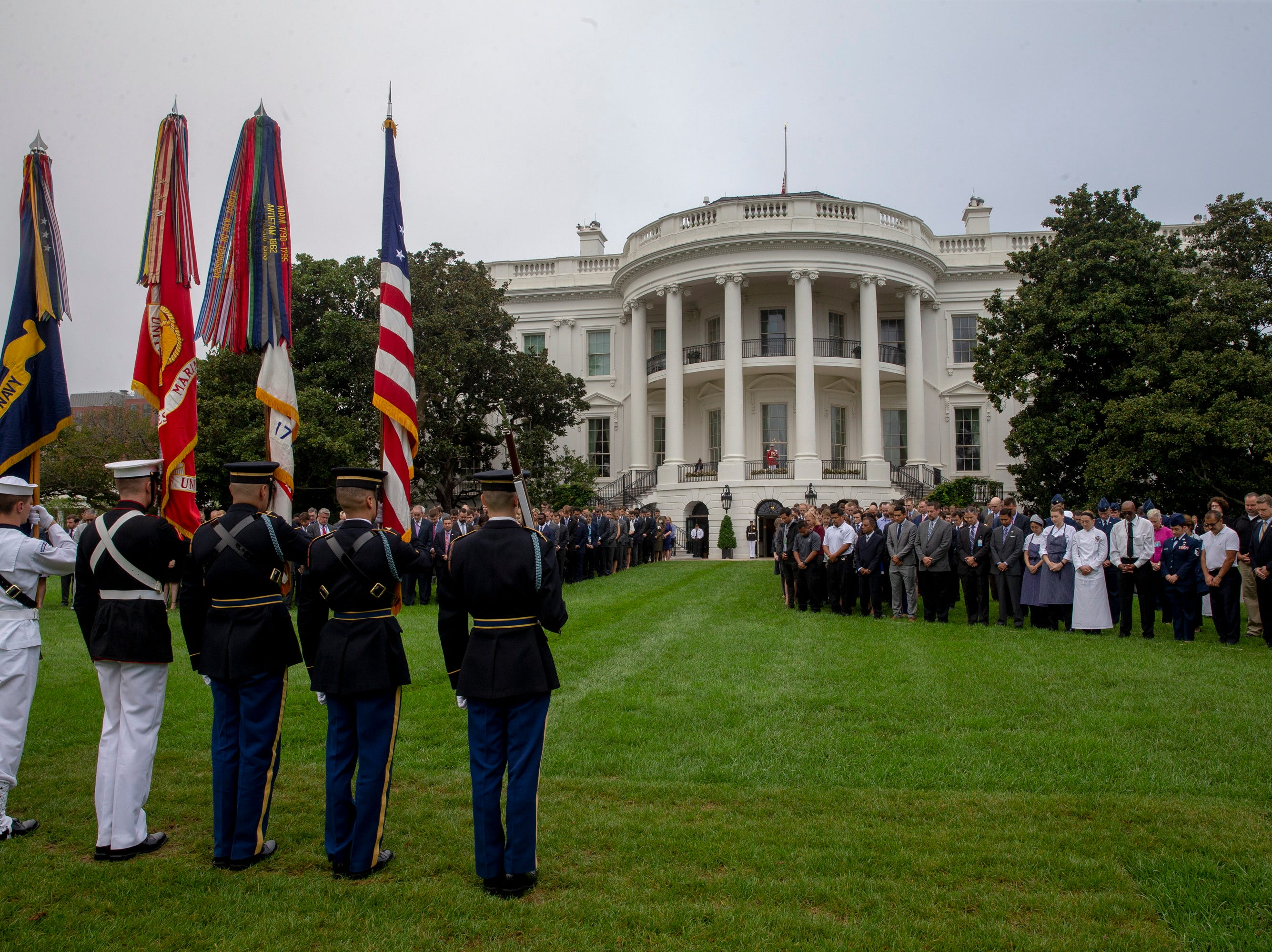 The Military Color guard presents the flag as staff gather on the on the South Lawn of the White House for a moment of silence in Washington.