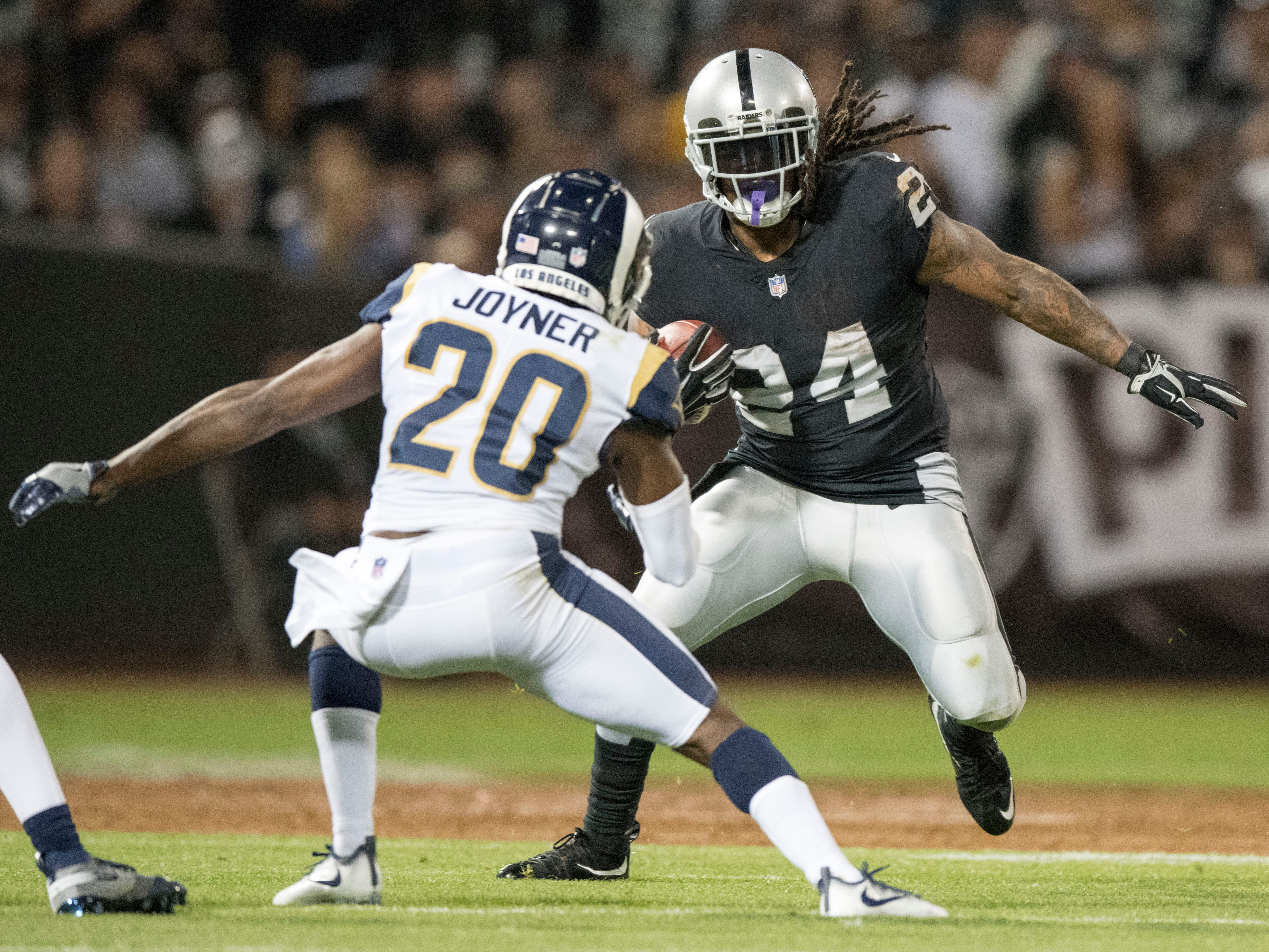 Oakland Raiders running back Marshawn Lynch runs the football against Los Angeles Rams safety Lamarcus Joyner during the first quarter at Oakland Coliseum.