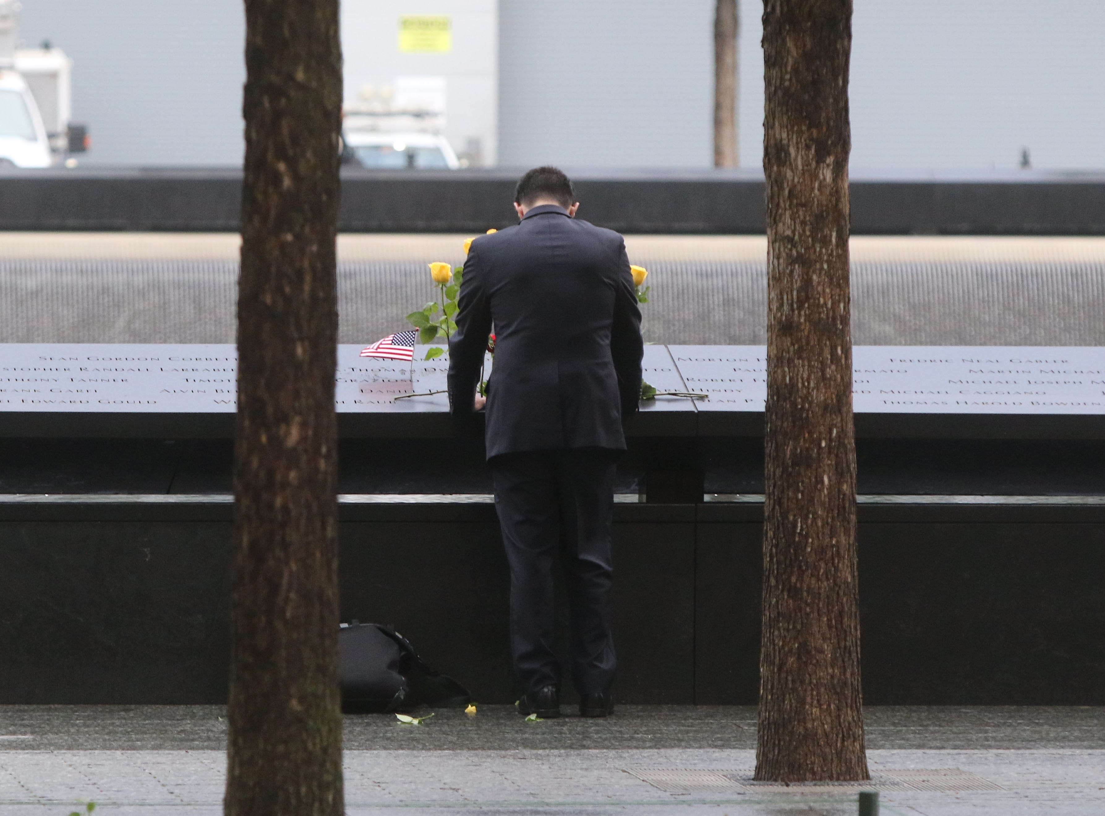 A man looks at names etched into granite at the National September 11 Memorial on Sept. 11, 2018 in New York.