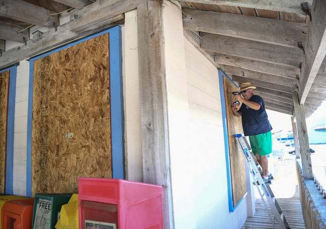 Jon Wright, 63, of Wilmington, N.C., drills screws in plywood to cover windows at the Causeway Cafe in Wilmington, N.C., on Tuesday, September 11, 2018. Hurricane Florence is expected to arrive in Wilmington late Thursday night through Friday morning.