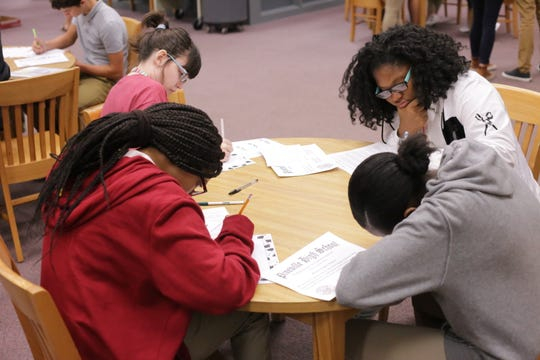 """(From left) Pineville High School freshmen Camille Verzwyvelt, Amerial Washington, Makaia Watson and Aziah Welch write letters to their future selves that they will open as seniors. The exercise was part of the school's third annual """"Commitment to Commencement."""""""
