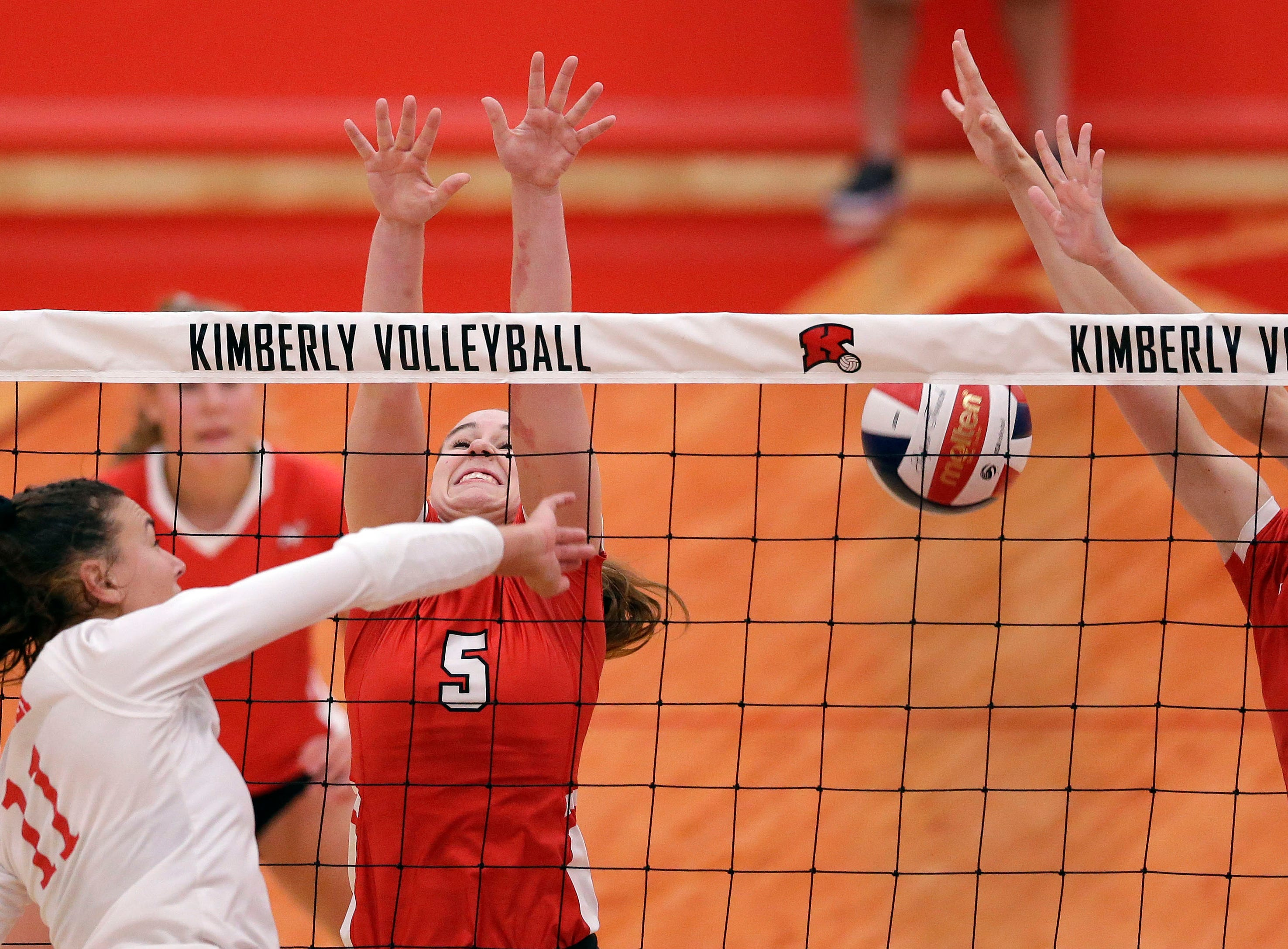 Maggie Cartwright of Kimberly hits between Tommy Albers, left, and Reagan Obry of Neenah in FVA girls volleyball Tuesday, September 11, 2018, at Kimberly High School in Kimberly, Wis.Ron Page/USA TODAY NETWORK-Wisconsin