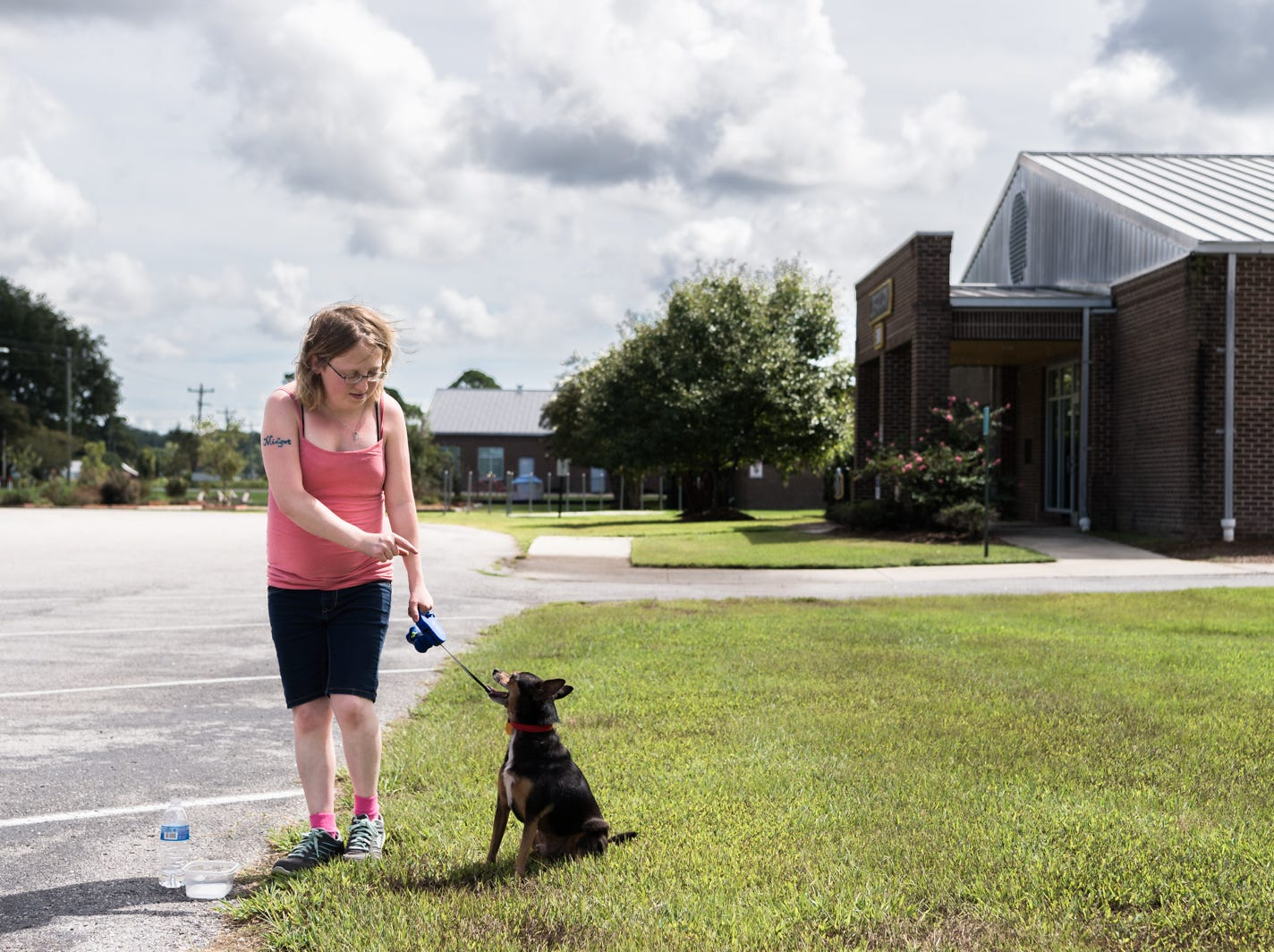 Kelly Rathburn waits with her dog Spud before leaving on a bus to Knightdale high school in Knightdale, a suburb of Raleigh before Hurricane Florence makes landfall, Sept. 12, 2018. A storm surge of about three to six feet is expected for Swan Quarter, and around six feet for Ocracoke Island with 12-20 inches of rainfall for the entire area. Hyde county as well as several surrounding counties are under mandatory evacuation.