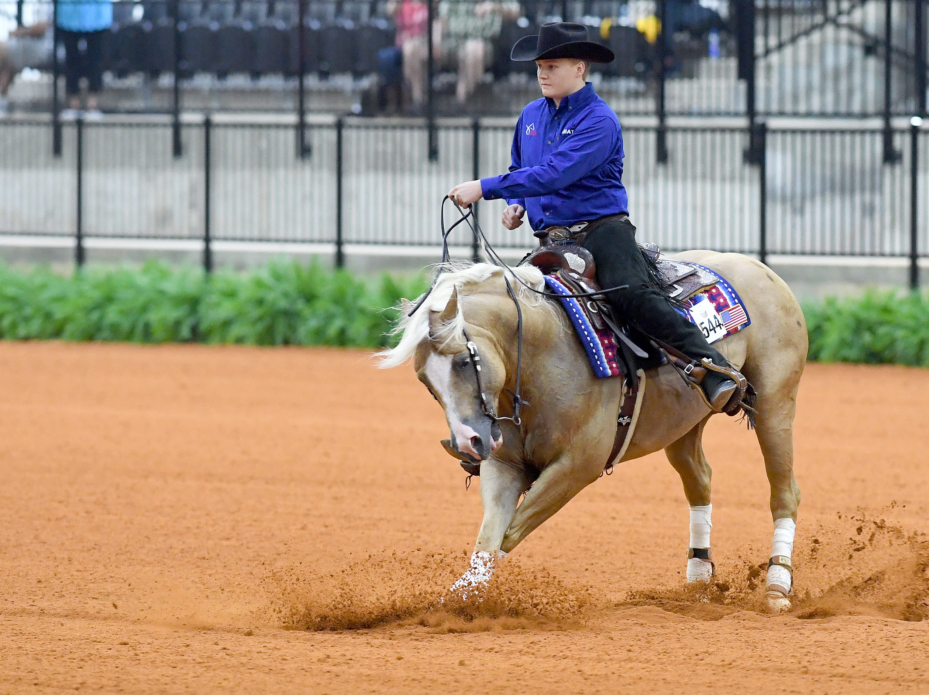 Cade Mccutcheon, with his horse, Custom Made Gun, competes in the reining competition during the FEI World Equestrian Games at the Tryon International Equestrian Center on Sept. 12, 2018. A score of 229 put him in the lead for the morning's competition lineup. He is the youngest United States athlete in the games at 18-years-old.