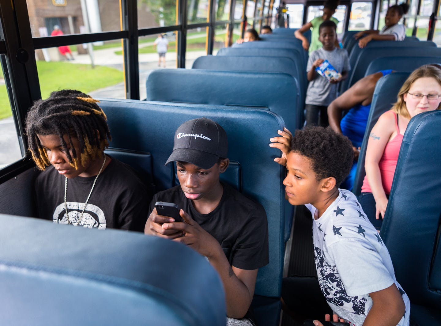 Chris Johnson, 13, Tyler Seoby, 14, and Shubert Johnson, 11, play on their phones on a bus leaving for Knightdale high school in Knightdale, a suburb of Raleigh before Hurricane Florence makes landfall Sept. 12, 2018. A storm surge of about three to six feet is expected for Swan Quarter, and around six feet for Ocracoke Island with 12-20 inches of rainfall for the entire area. Hyde county as well as several surrounding counties are under mandatory evacuation.