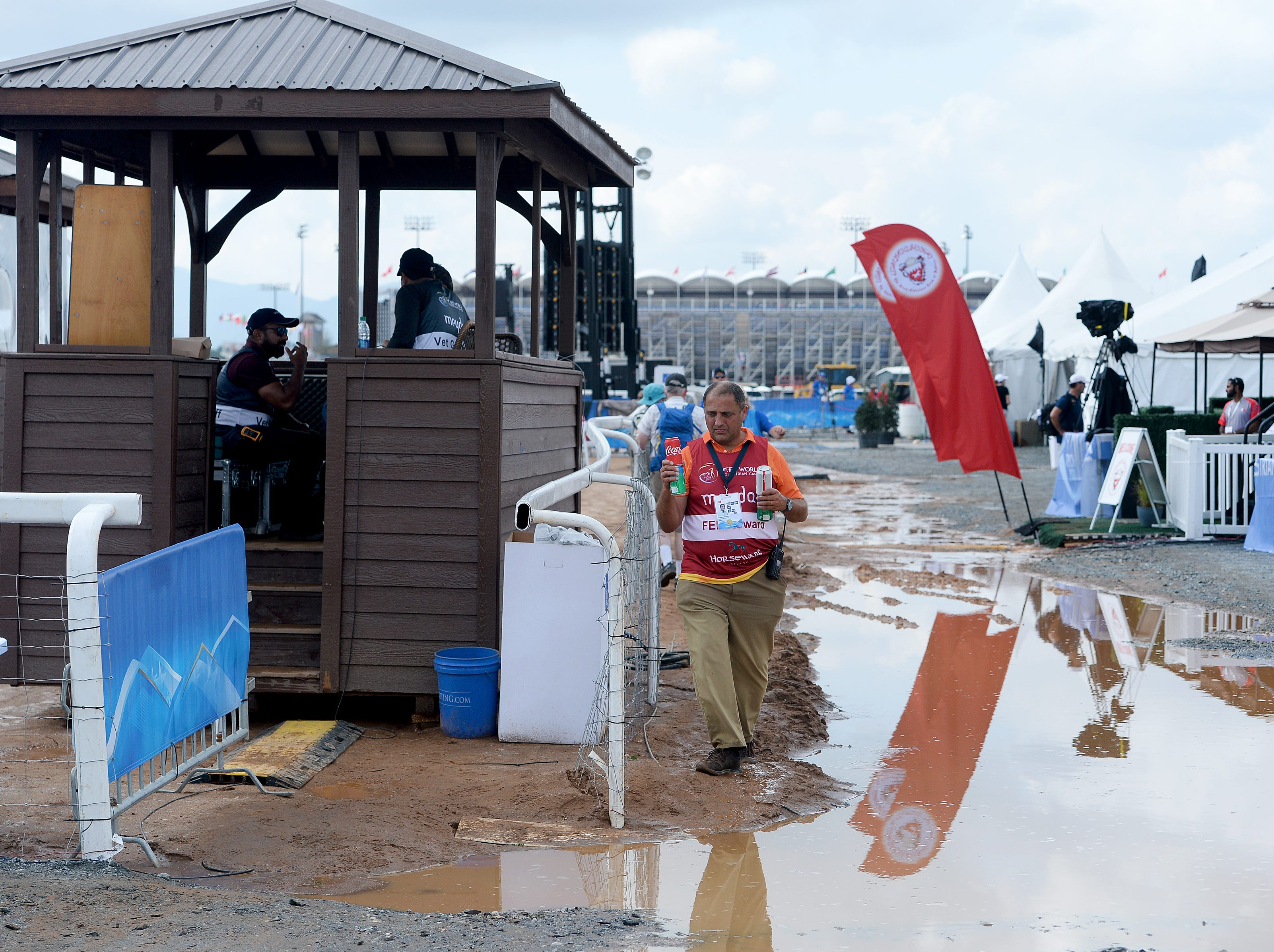 An official makes his way around a large puddle at the Endurance course during the FEI World Equestrian Games at the Tryon International Equestrian Center on Sept. 12, 2018.