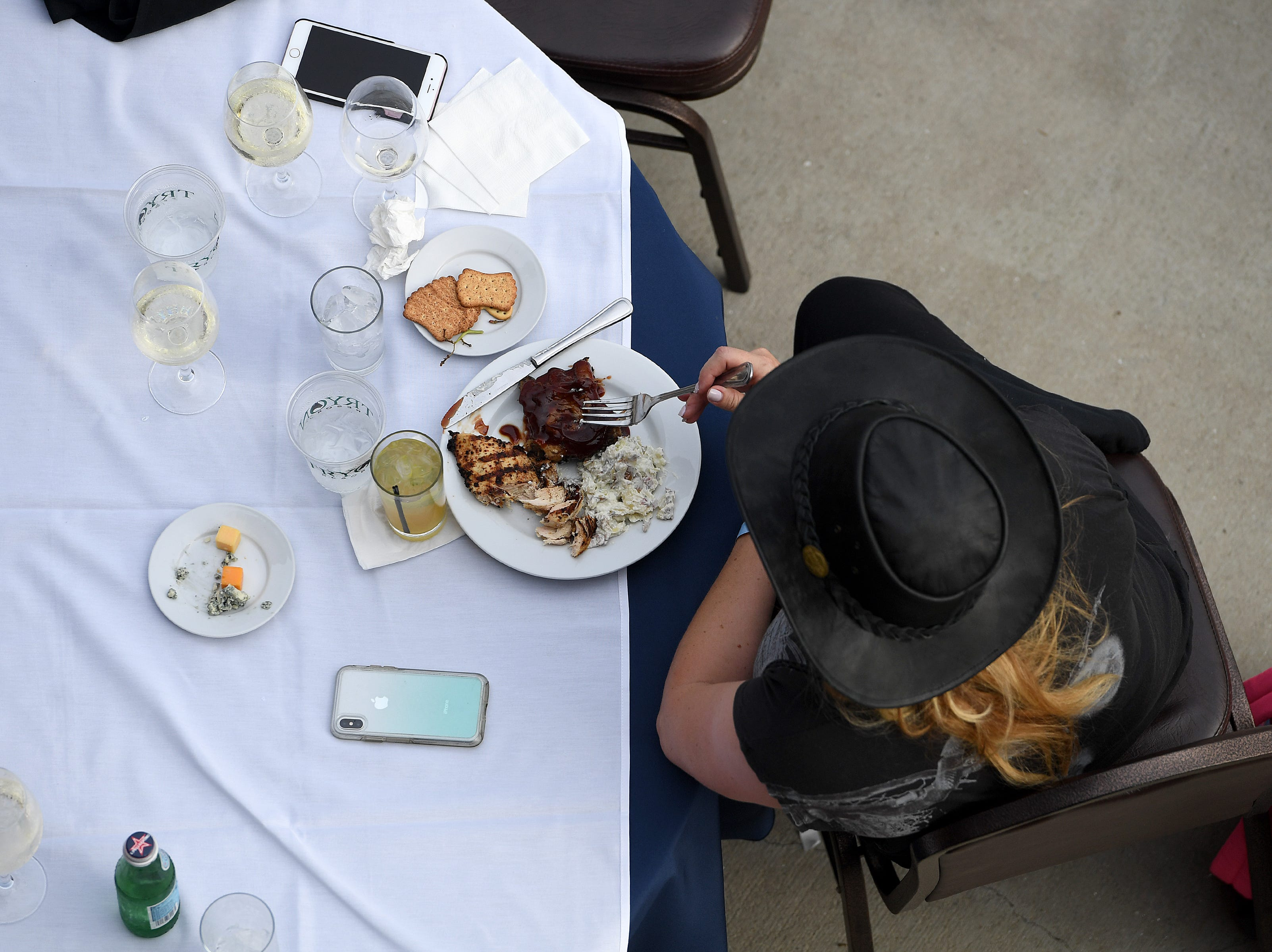 A woman eats dinner at the ring-side restaurant during the opening ceremony for the FEI World Equestrian Games at the Tryon International Equestrian Center on Sept. 11, 2018.