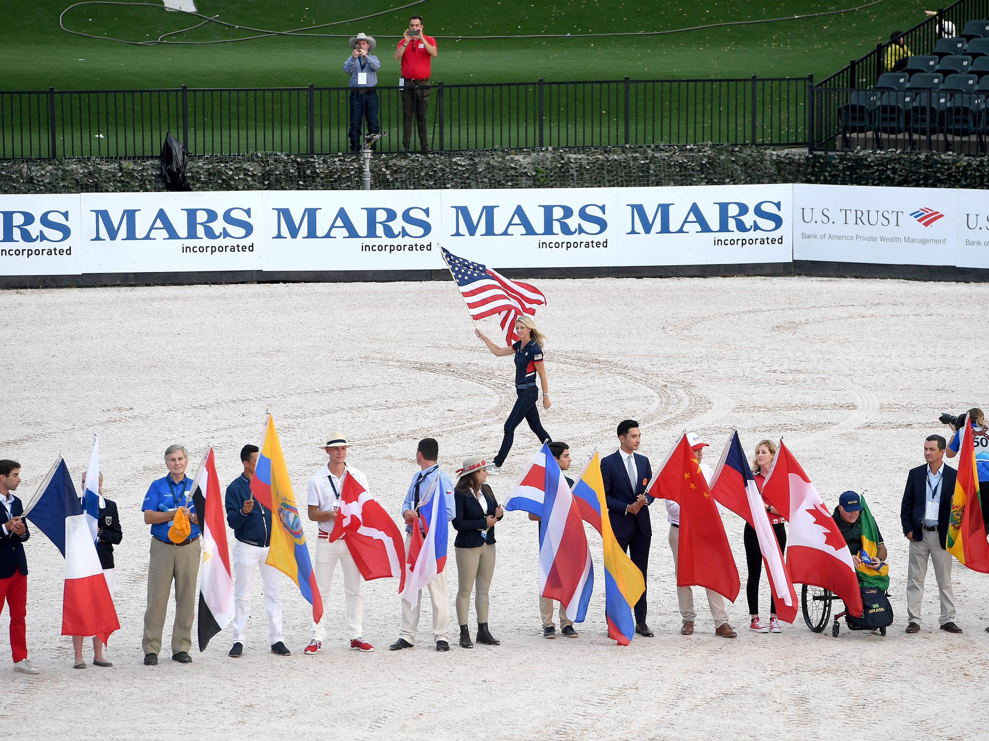 American dressage athlete Laura Graves parades with the American flag during the opening ceremony for the FEI World Equestrian Games at the Tryon International Equestrian Center on Sept. 11, 2018.