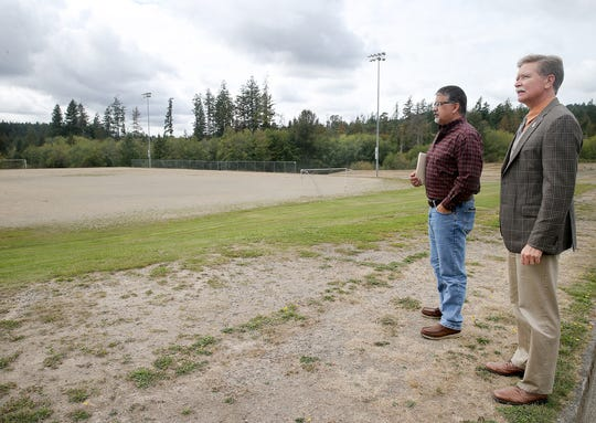 Bremerton mayor Greg Wheeler, right, and Jeff Elevado, director of the Bremerton Parks and Recreation Department, look one of the sand soccer fields at Pendergast Park in Bremerton. The city will apply for money to add turf to the park's fields.