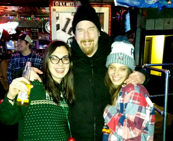 Ryan Murphy, center, poses with Karolina Madden, left, and Kelcie Morris at Ruben James sports bar on Dec. 18, 2017.
