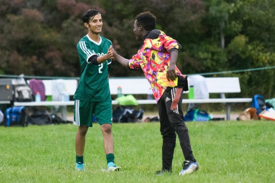 Winooski's Lek Nath Luitel (2) and goalie Ekyod Lumambo high five during the boys soccer game between Danivlle and Winooski at Winooski High School on Tuesday night September 11, 2018 in Winooski.