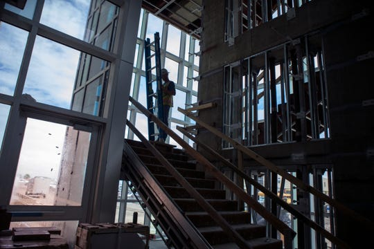 """A subcontractor works on the """"monumental stair"""" at Texas A&M University-Corpus Christi's Tidal Hall on September 12, 2018. Tidal Hall, a $60 million three-story building scheduled to open in the fall, will support two of the university's fastest growing programs in the college of science and engineering."""