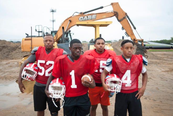 Senior members of the Pennsauken High School football team, from left, Arthur Carter, Donte Jamison, Nahzir Russell, and Darrien Tabb stand by the Pennsauken High School football field that is currently under construction.