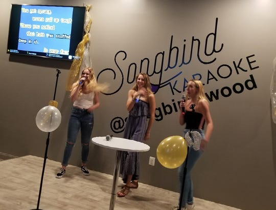 Simone Kelsall (left), Nora Woods and Lena Kelsall form a girl group during a graduation party at Songbird Karaoke.