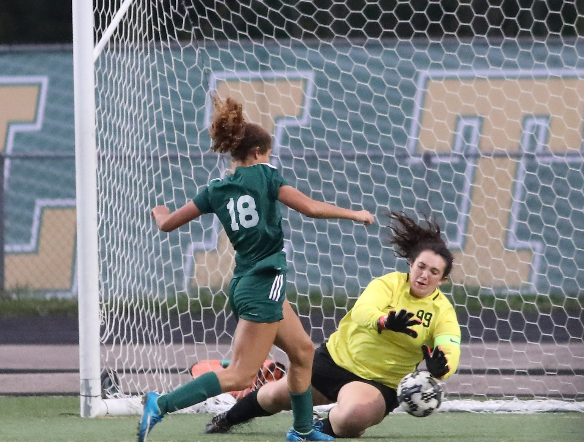 Little Miami's Kayna Grimes scores a goal past Ross goalie Kellan Romans during their soccer game, Tuesday, Sept. 11, 2018.