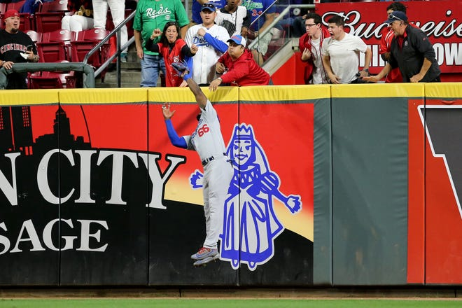 Los Angeles Dodgers right fielder Yasiel Puig (66) leaps to catch a fly ball in the fifth inning  during a baseball game between the Los Angeles Dodgers and the Cincinnati Reds, Tuesday, Sept. 11, 2018, at Great American Ball Park in Cincinnati.