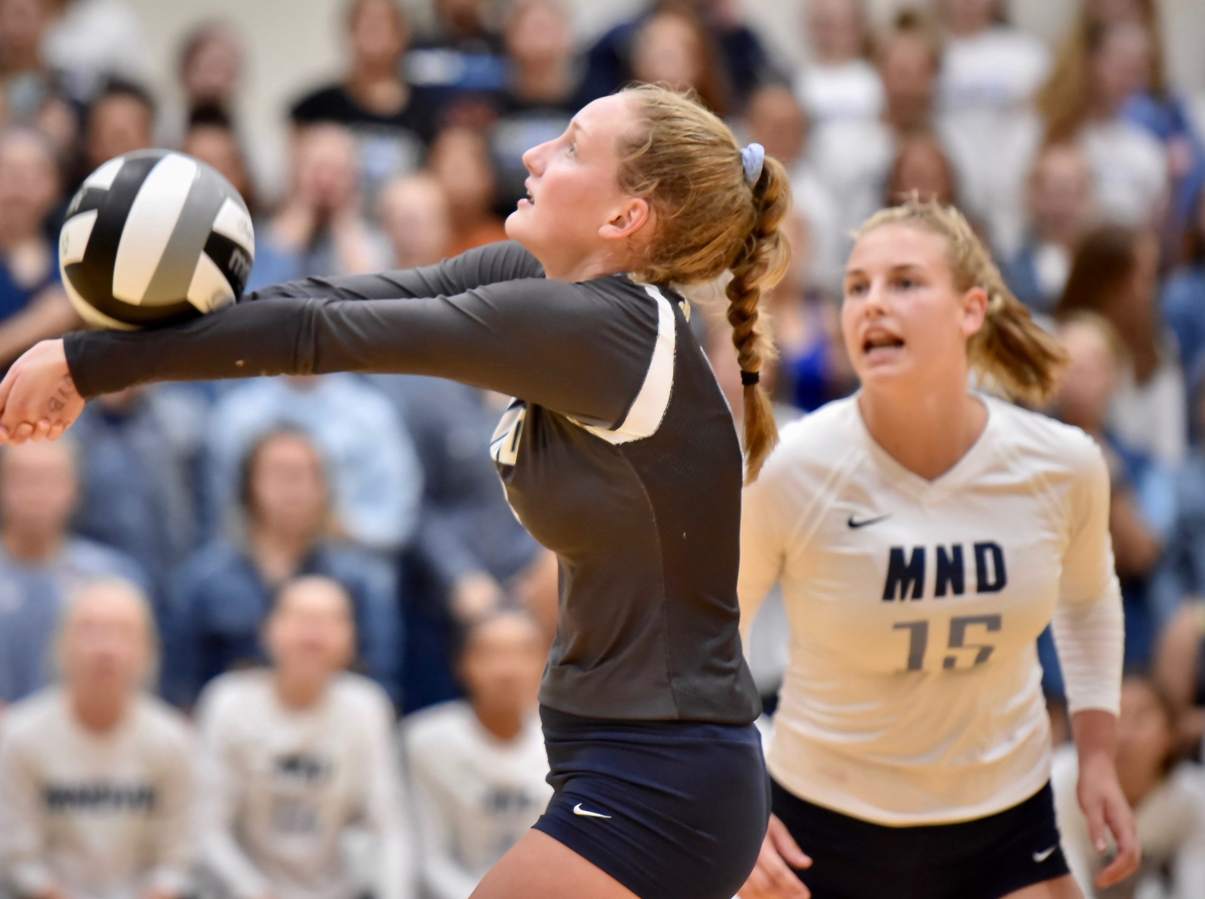 Mount Notre Dame's Emily Ernst bumps the ball to a teammate against Ursuline Tuesday, Sept. 11, 2018 at Ursuline Academy