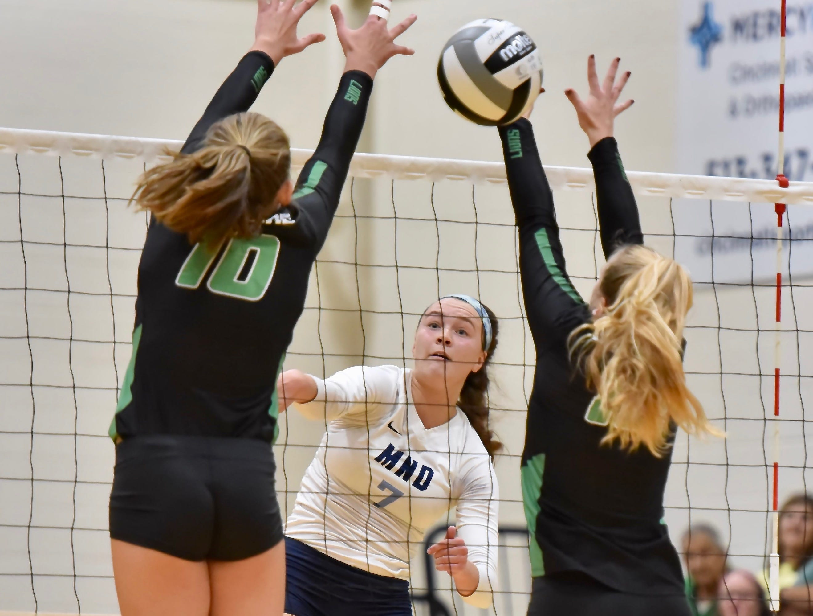 Mount Notre Dame's Olivia Marklay spikes the ball past two Ursuline defenders Tuesday, Sept. 11, 2018 at Ursuline Academy