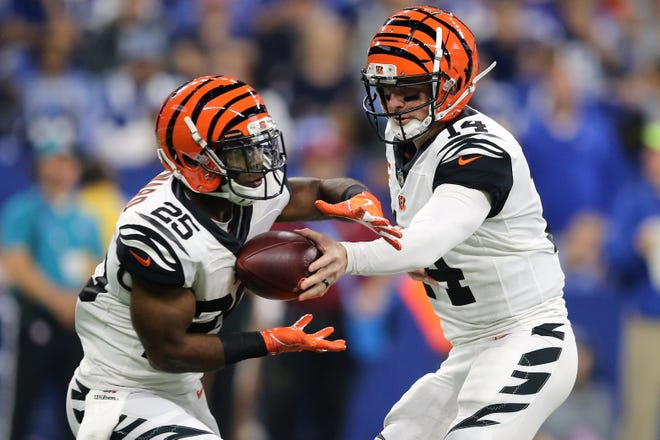 Cincinnati Bengals quarterback Andy Dalton (14) hands the ball off to Cincinnati Bengals running back Giovani Bernard (25) in the second quarter during the Week 1 NFL game between the Cincinnati Bengals and the Indianapolis Colts, Sunday, Sept. 9, 2018, at Lucas Oil Stadium in Indianapolis.