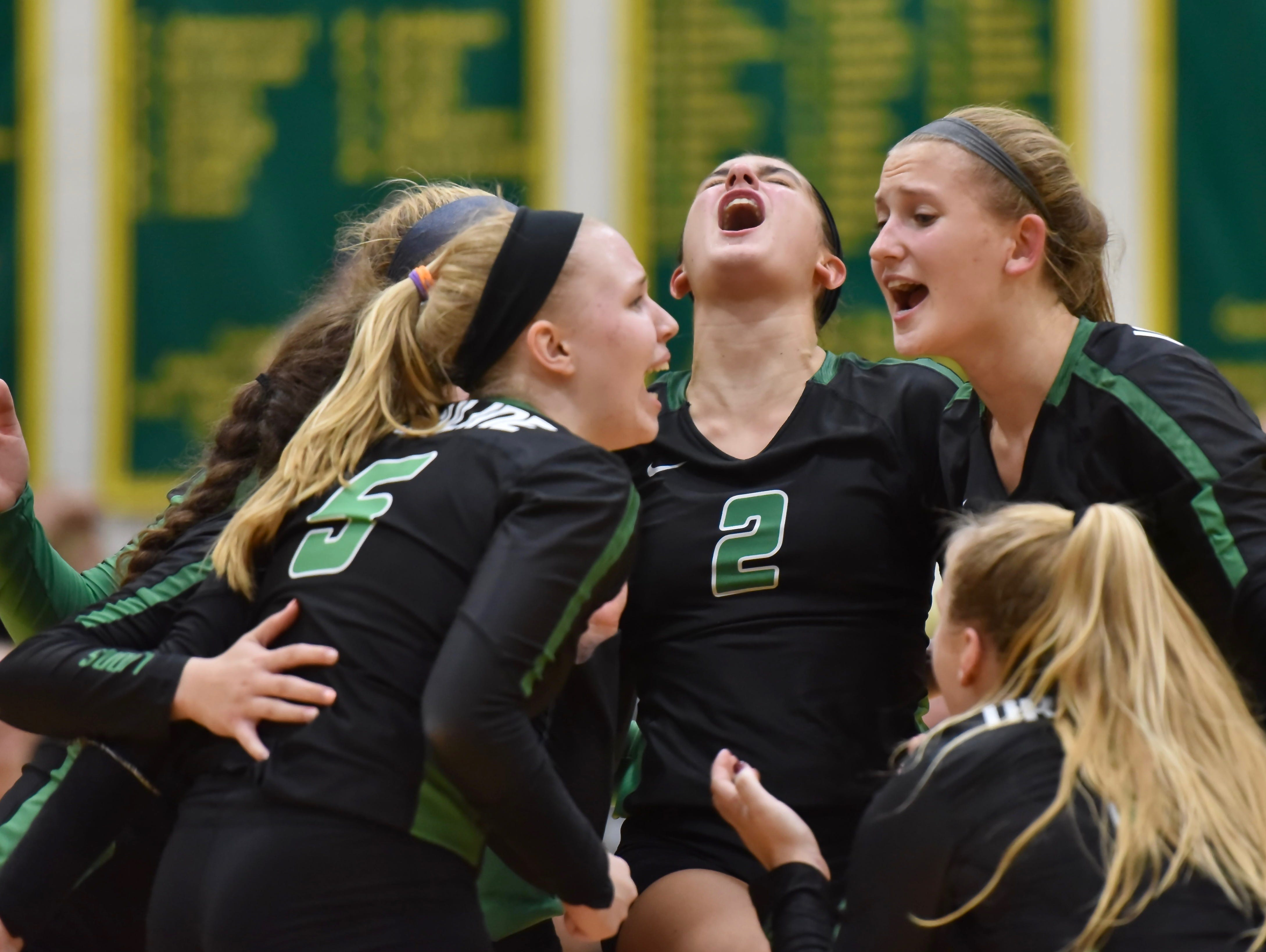 The Ursuline Lions celebrate a victory in the fourth set against MND, forcing a fifth and decisive set Tuesday, Sept. 11, 2018 at Ursuline Academy