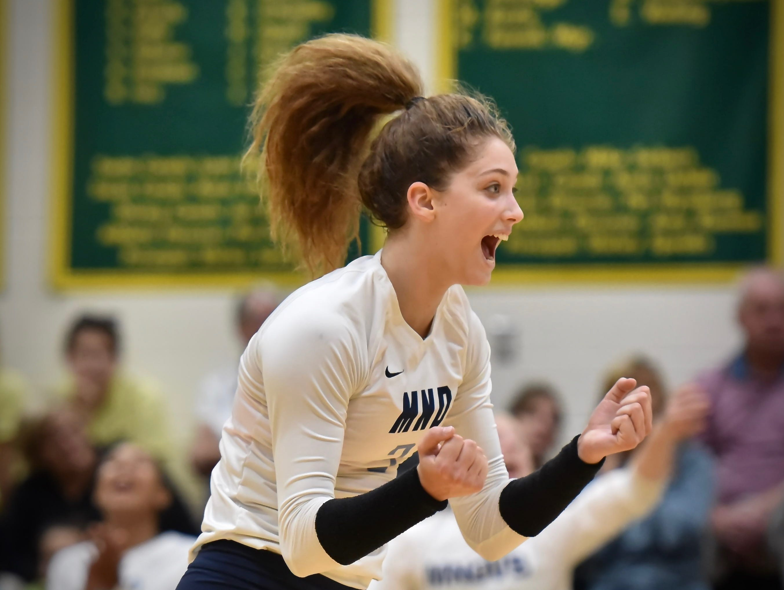 Sam Wolf celebrates a second set victory for Mount Notre Dame over Ursuline Academy Tuesday, Sept. 11, 2018 at Ursuline Academy