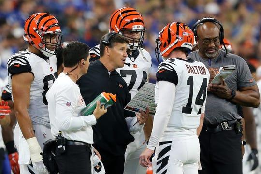 Cincinnati Bengals offensive coordinator Bill Lazor, center, talks with Cincinnati Bengals quarterback Andy Dalton (14) in the fourth quarter during the Week 1 NFL game between the Cincinnati Bengals and the Indianapolis Colts, Sunday, Sept. 9, 2018, at Lucas Oil Stadium in Indianapolis. Cincinnati won 34-23.