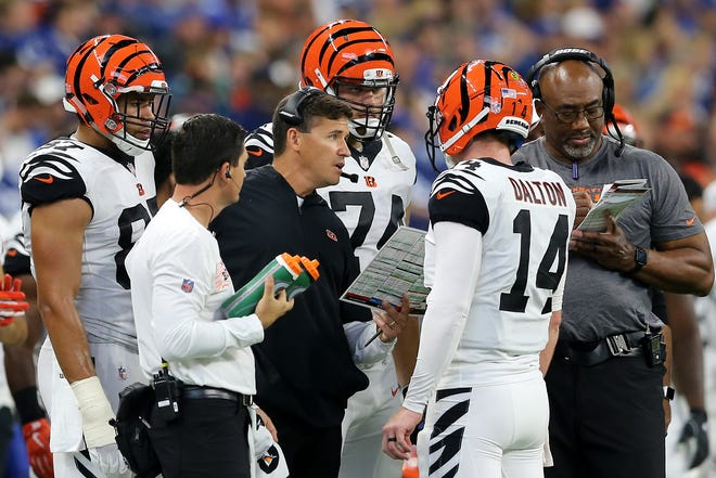 Cincinnati Bengals offensive coordinator Bill Lazor, center, talks with Cincinnati Bengals quarterback Andy Dalton (14) in the fourth quarter during the Week 1 NFL game between the Cincinnati Bengals and the Indianapolis Colts, Sunday, Sept. 9, 2018, at Lucas Oil Stadium in Indianapolis. Cincinnati won 34-23.