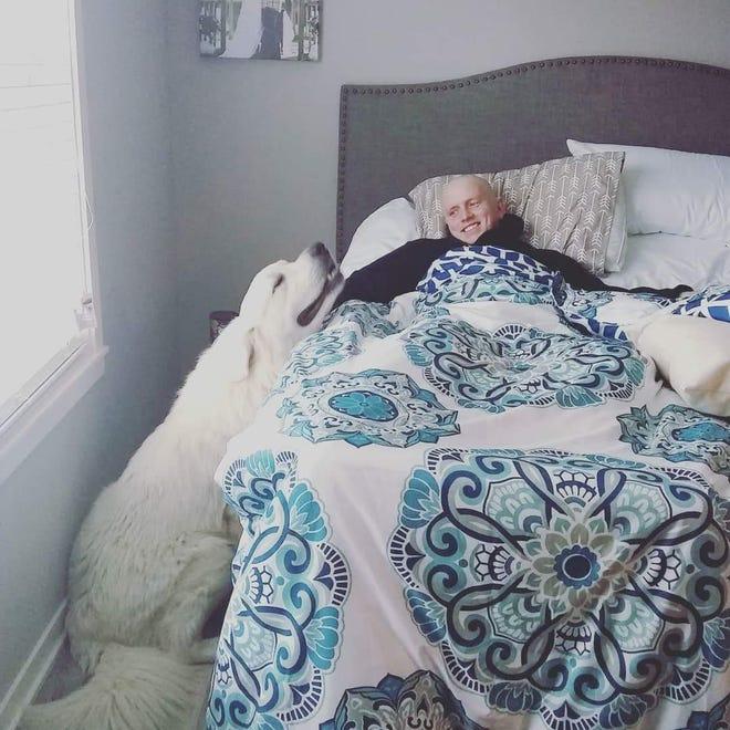 Brice Udelhoven, 26, of Mingo, lays with his dog, Mack.