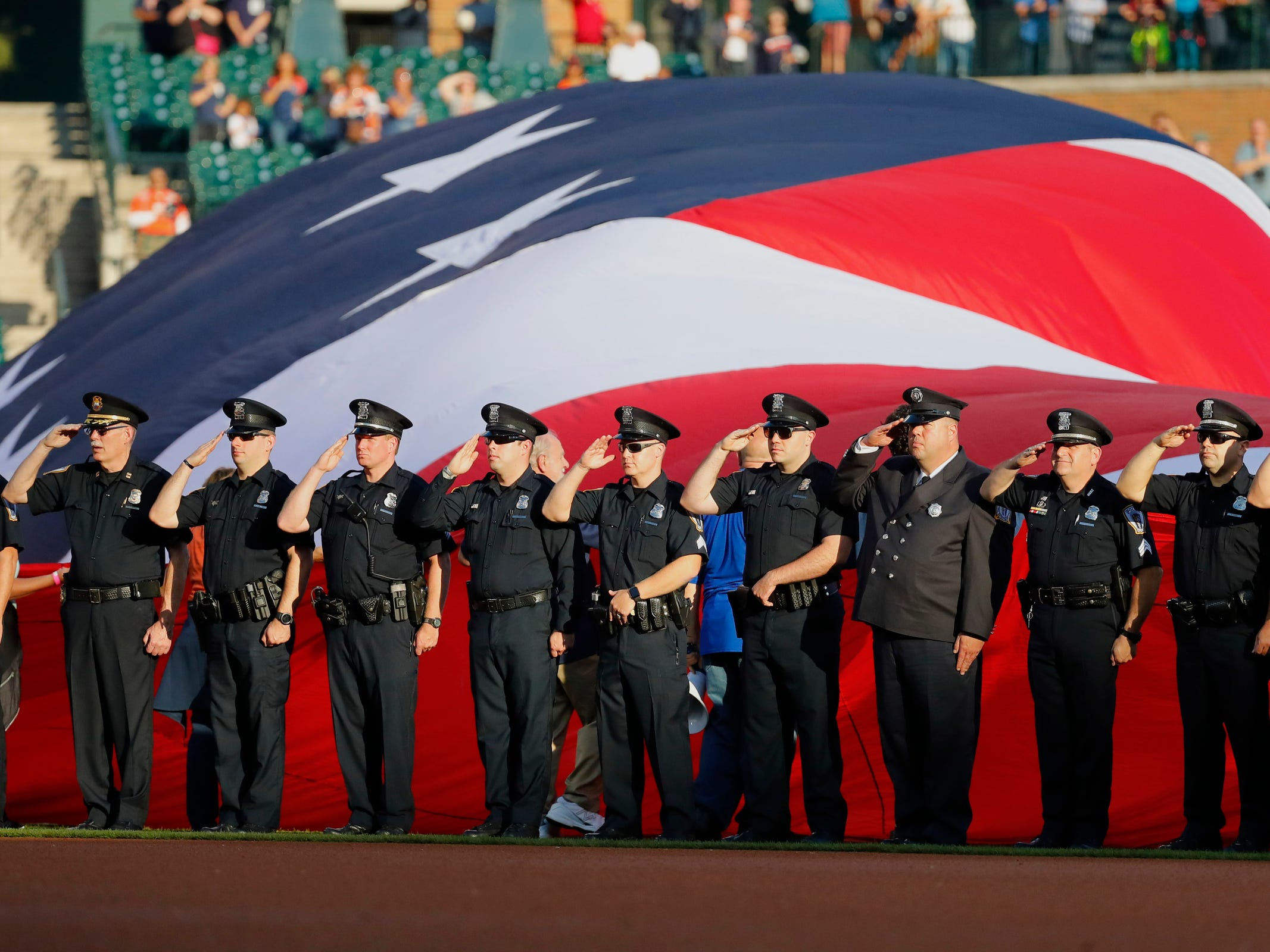 First responders salute during the national anthem prior to the game between the Detroit Tigers and the Houston Astros at Comerica Park, Tuesday, Sept. 11, 2018.
