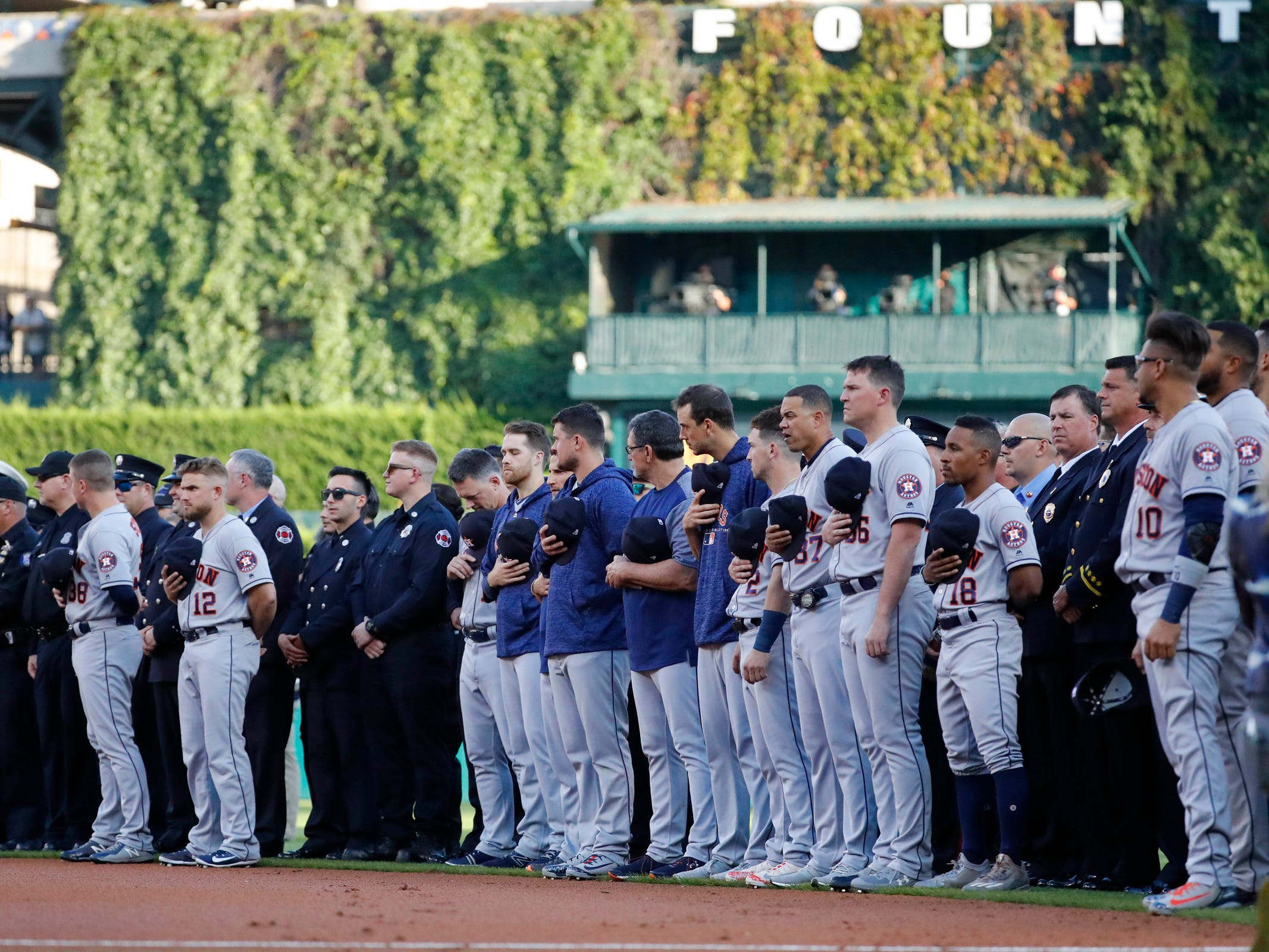 Houston Astros players line the field with first responders during the national anthem prior to the game against the Detroit Tigers at Comerica Park, Tuesday, Sept. 11, 2018.