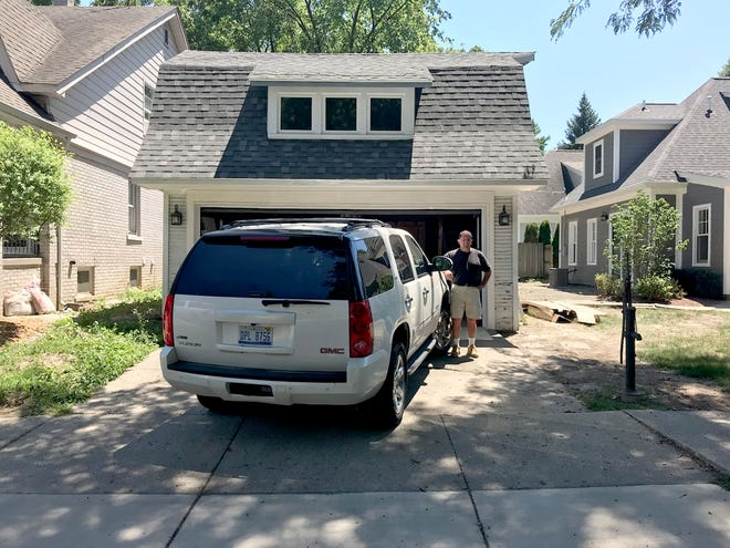"Builder Al Shaheen stands in front of a garage in Grosse Pointe on July 9, 2018 that he recently modified for Lorraine Dillon, so she could fit her GMC Yukon inside. ""There was not enough length to the driveway to park the car without blocking the sidewalk,"" Dillon said. ""The garage had to be usable."""
