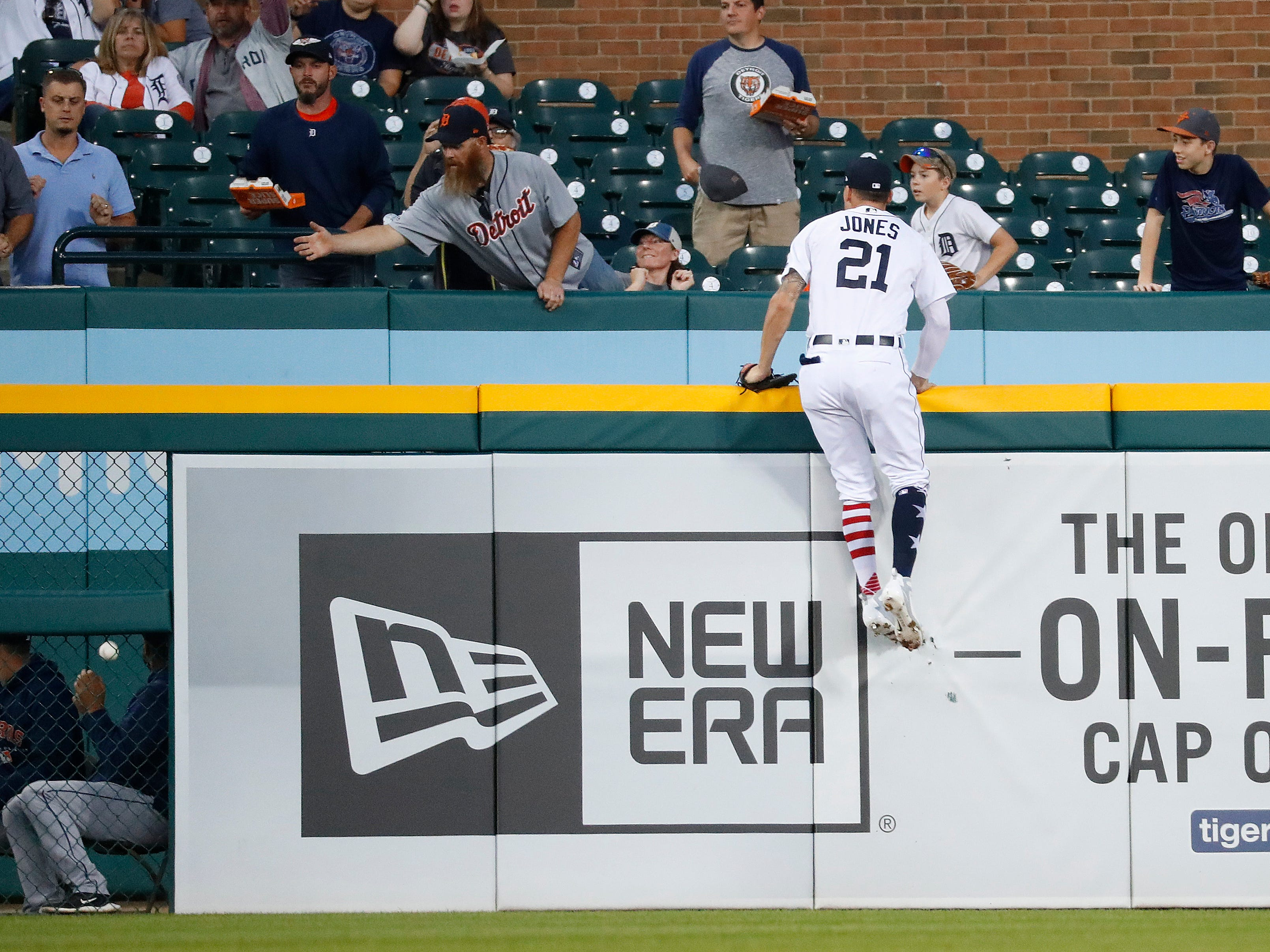 Detroit Tigers left fielder JaCoby Jones climbs the outfield wall but can't reach a Houston Astros' Tyler White two-run home run in the fourth inning of a baseball game against the Detroit Tigers in Detroit, Tuesday, Sept. 11, 2018.