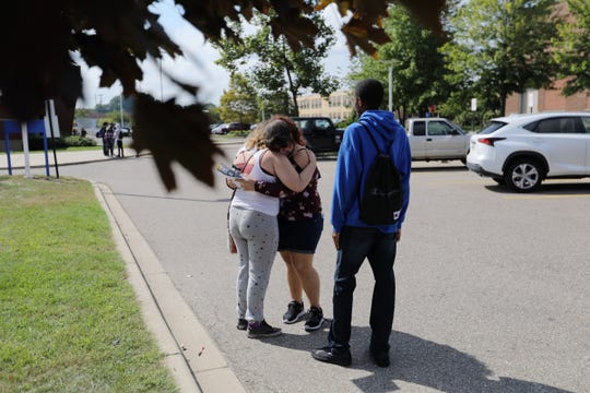 Victoria Oraczko, center, 16, of Warren, Michigan, is comforted by her friends after she was interviewed and released after the stabbing that occurred in her classroom at Fitzgerald High School in Warren on Wednesday, Sept. 12, 2018.