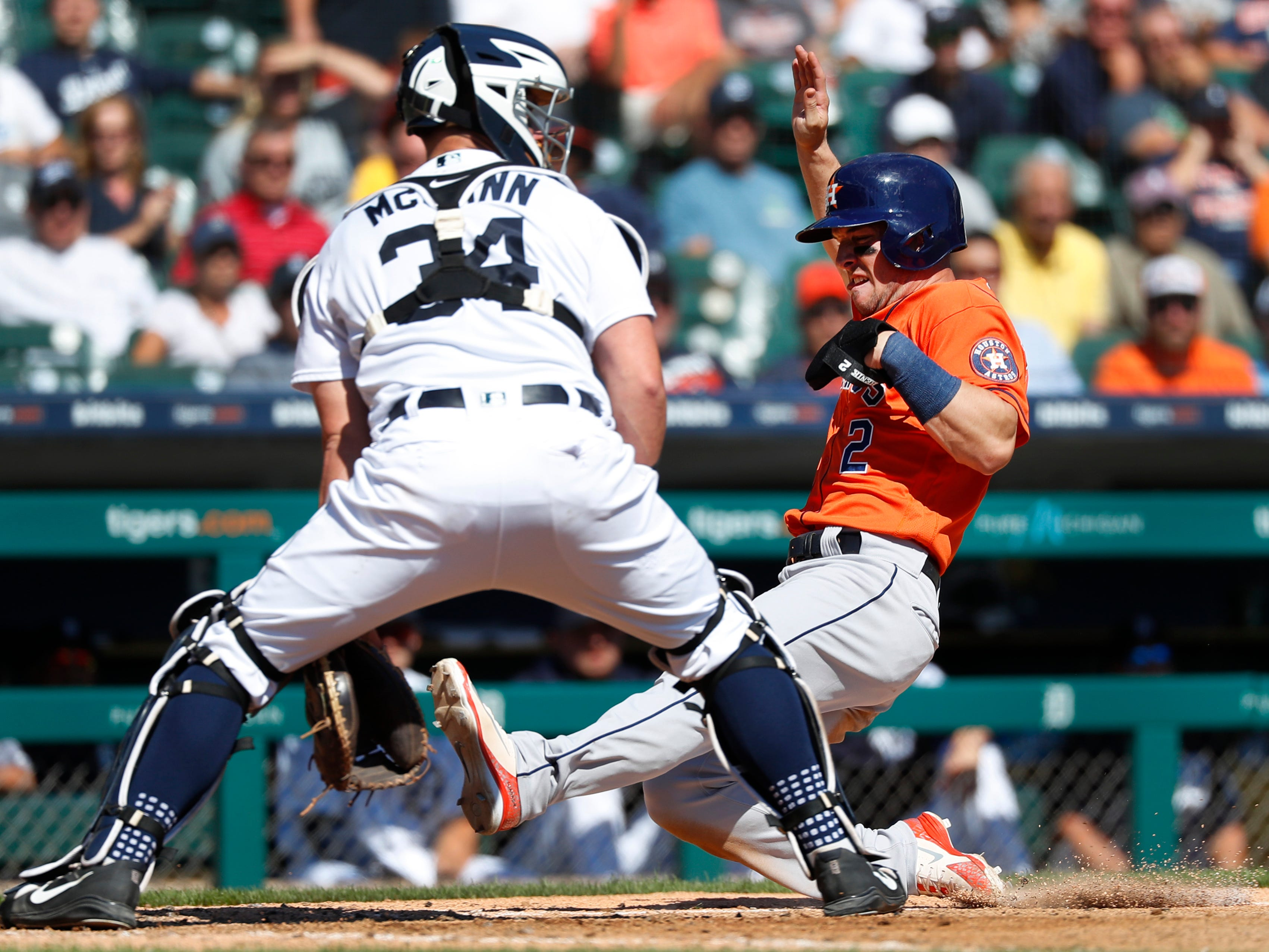 Houston Astros' Alex Bregman (2) scores at home plate as Detroit Tigers catcher James McCann (34) waits for the throw in the fifth inning.