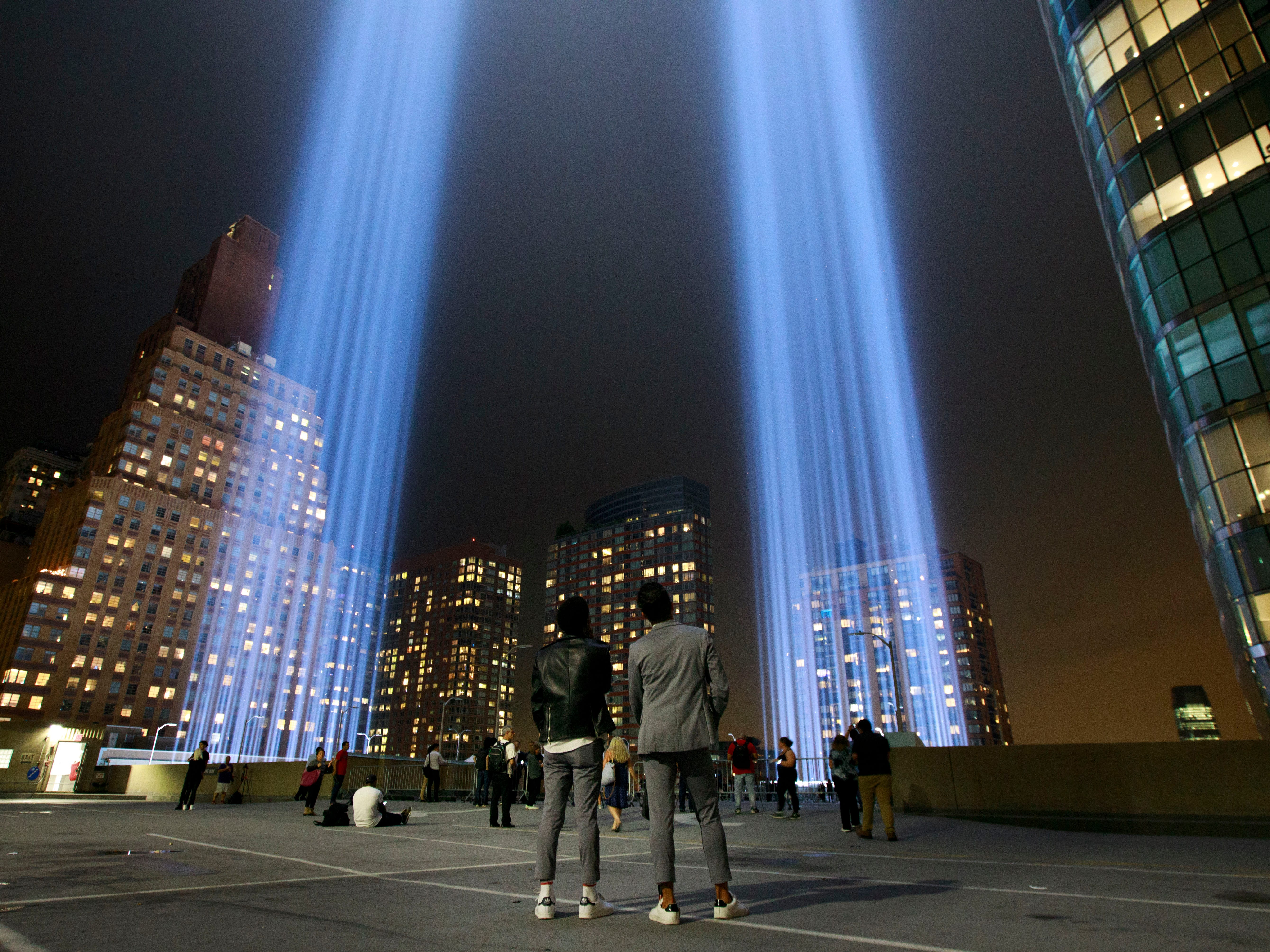 People observe the 'Tribute in Light' atop the Battery Parking Garage as it rises skyward in Lower Manhattan, September 11, 2018 in New York City. In New York City and throughout the United States, the country is marking the 17th anniversary of the September 11 terrorist attacks.
