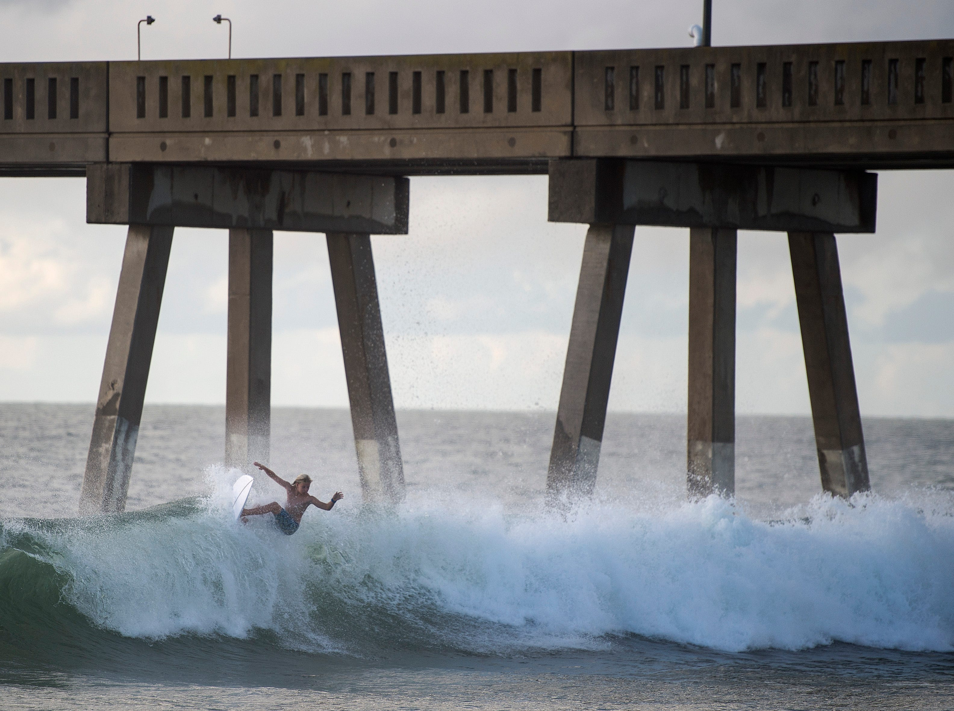 A surfer catches a wave a day before the arrival of Hurricane Florence at Wrightsville Beach, North Carolina on September 12, 2018.