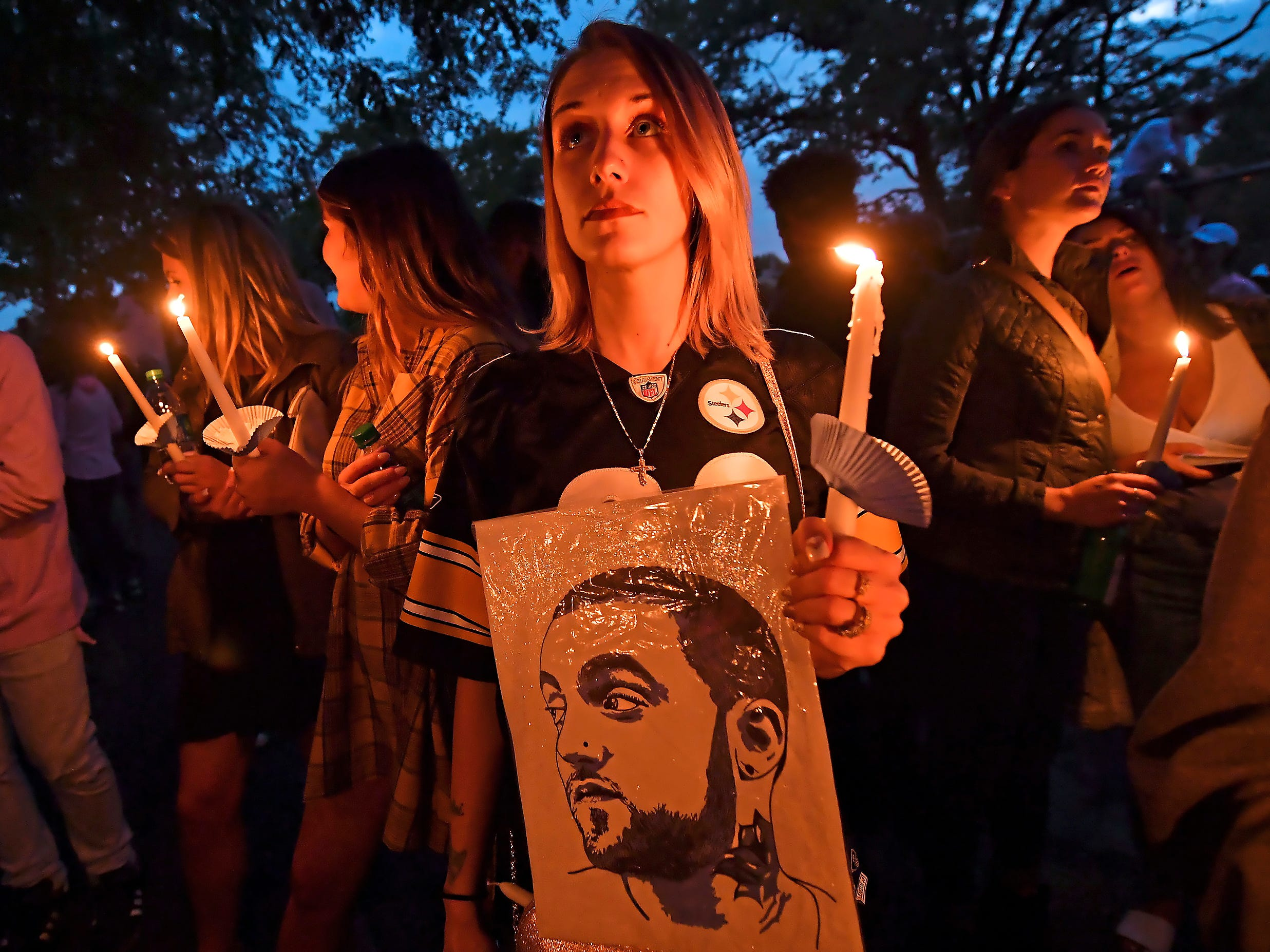 Andrea Grimm, 30, of the North Side neighborhood in Pittsburgh, holds a candle during a vigil for rapper Mac Miller, Tuesday, Sept. 11, 2018, at Blue Slide Park in Pittsburgh. Blue Slide Park was the name of Miller's debut studio album. He died last week in California.