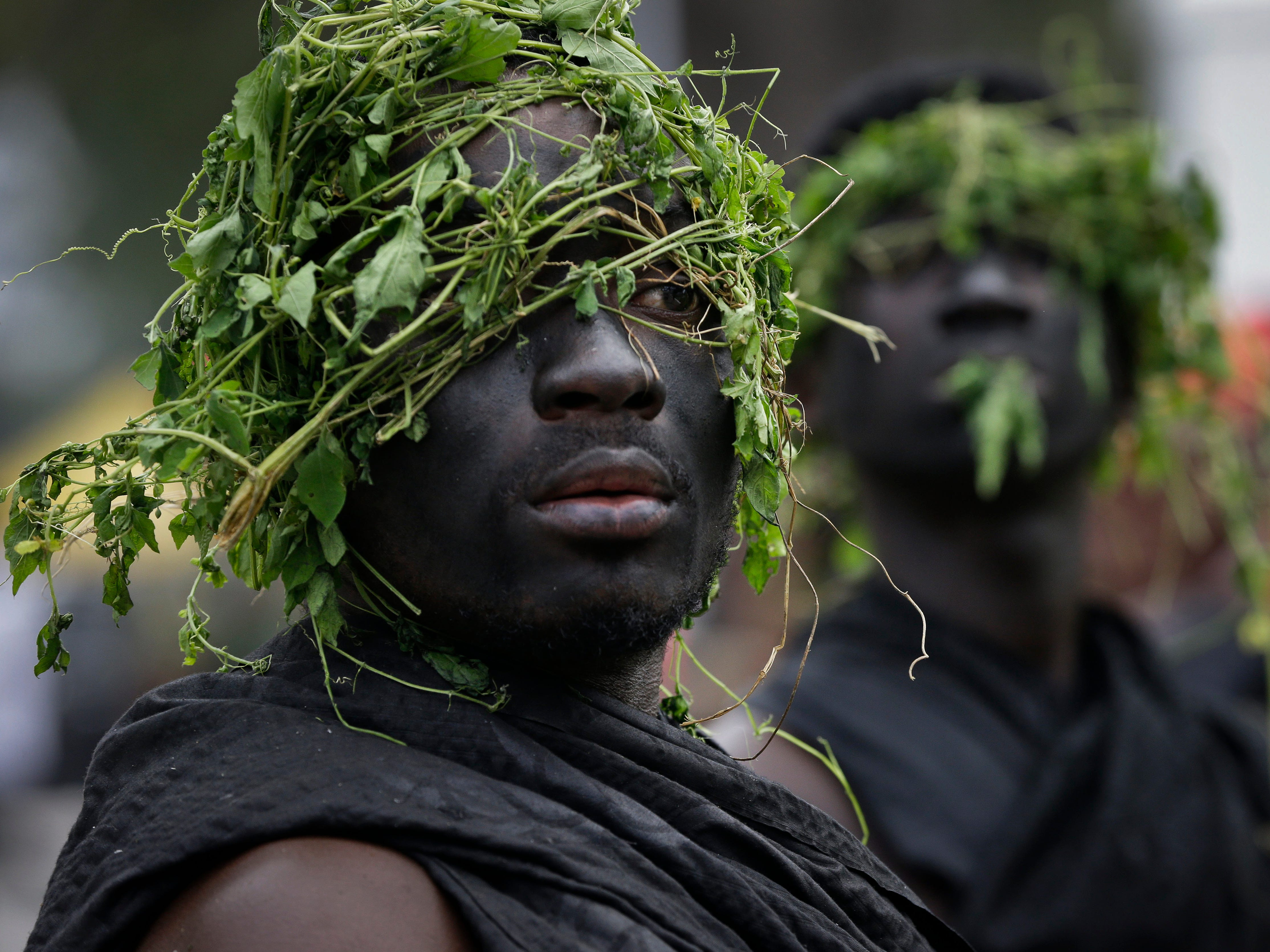Guards of a Ghanaian chief wear black and plants on their heads, a tradition when going to a funeral, and queue outside to pay their respects as the coffin of former U.N. Secretary-General Kofi Annan lies in state at the Accra International Conference Center in Ghana Wednesday, Sept. 12, 2018. Ghanaians are paying their respects to Annan, who died in August in Switzerland at age 80, ahead of Thursday's state funeral.