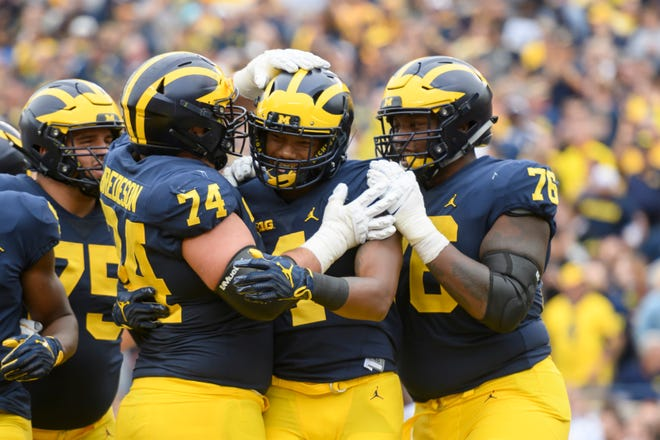 From left, Michigan offensive lineman Ben Bredeson, wide receiver Nico Collins, and offensive lineman Juwann Bushell-Beatty celebrate Collins' second-quarter touchdown reception against Western Michigan.