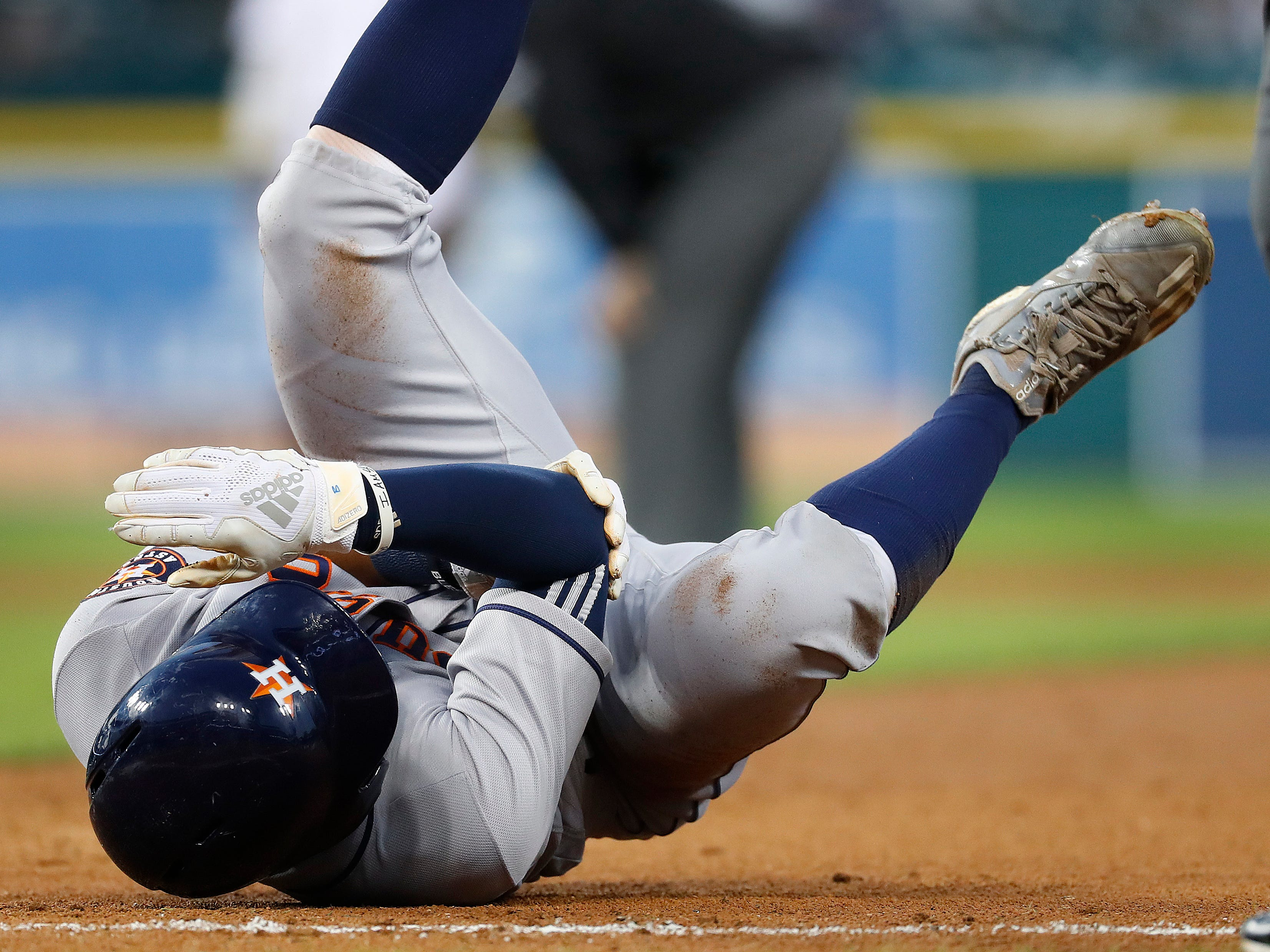 Houston Astros' Tony Kemp holds his arm after being hit by a throw at first base in the fourth inning.