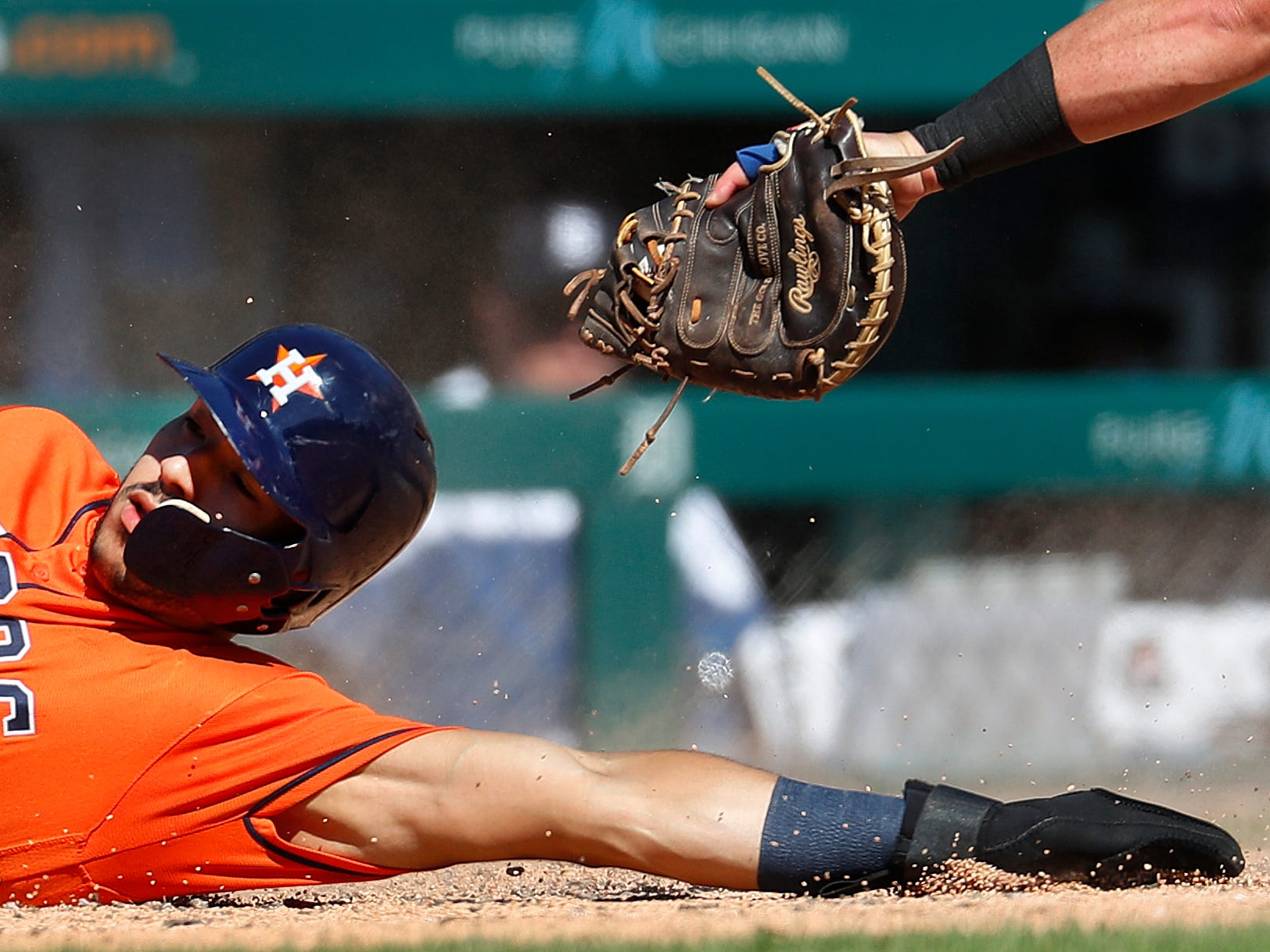 Houston Astros' Carlos Correa (1) slides safely into home plate as Detroit Tigers catcher James McCann's tag is late in the fifth inning.