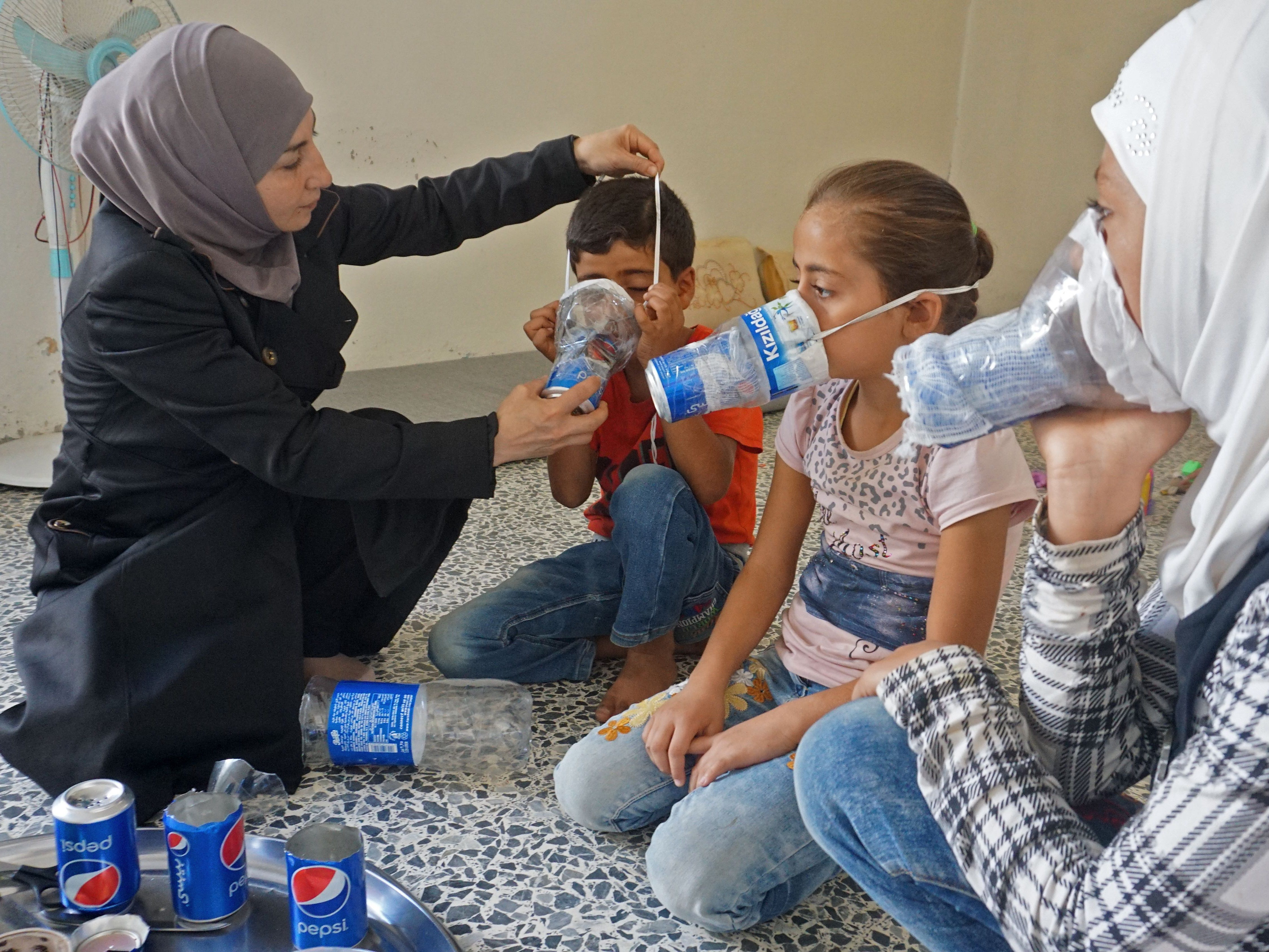 Um Majid (L) tries an improvised gas mask on familiy members in her home in Binnish in Syria's rebel-held northern Idlib province as part of preparations for any upcoming raids on September 12, 2018. - The Syrian regime and its Russian ally are threatening an offensive to retake the northwestern province of Idlib, Syria's last rebel bastion.