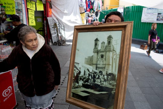 Rosa Maria Ubaldo Lopez looks at an 1910 photograph of her neighborhood, where the oldest building is located in Mexico City. Ubaldo Lopez, 79, was born in that building at 25 Manzanares Street in 1938.