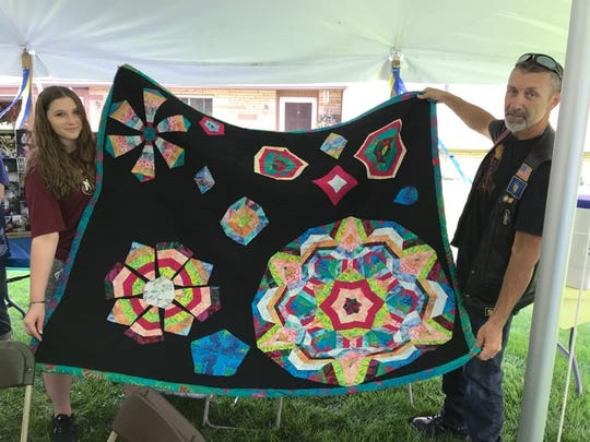 Ashley Matteson, daughter of accident victims Harolyn and Mathew Matteson, holds up Pat Holstrum's homemade quilt, presented by Joe Sullivan of the Horseheads American Legion.