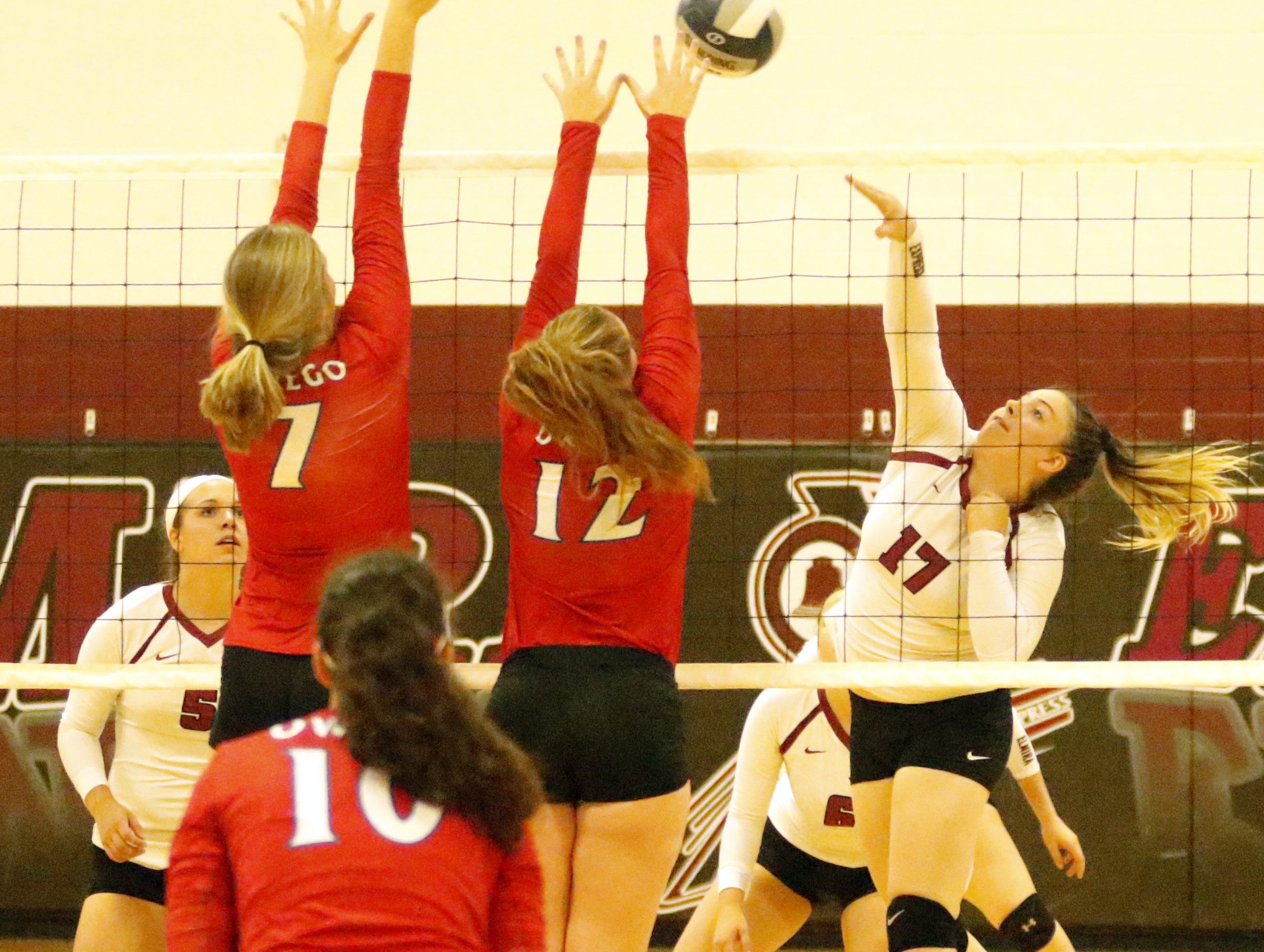 Makena Craig of Elmira goes up for a kill as Owego's Sara Zepkowski (7) and Taylor Aubel (12) defend during OFA's 3-0 win Sept. 11, 2018 at Elmira High School.